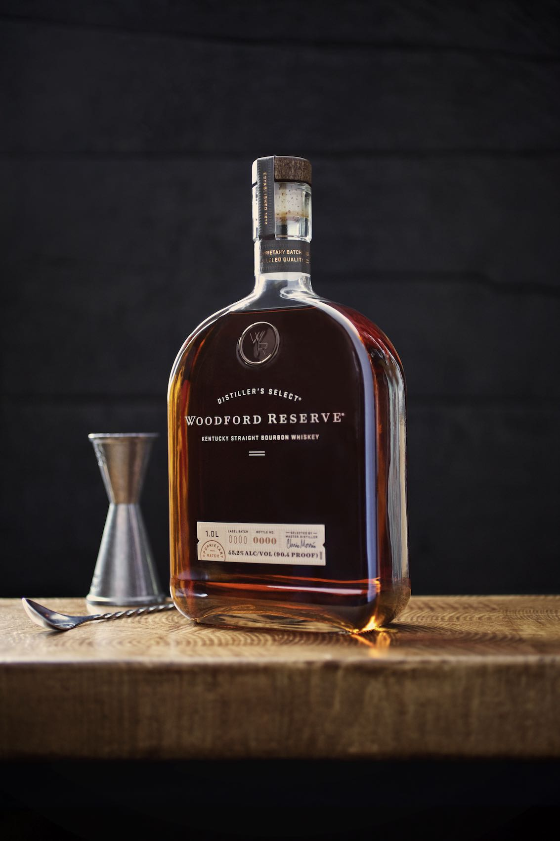 Jody Horton Photography - Woodford Reserve Bourbon Whiskey Ad with bottle on wooden surface with jigger and swizzle.