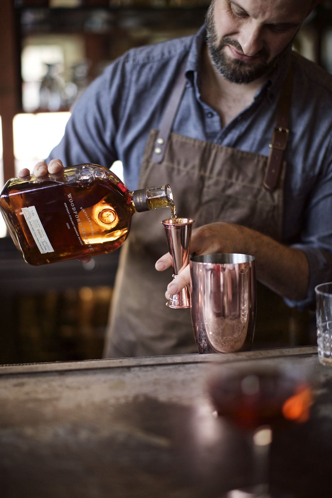 Jody Horton Photography - Woodford Reserve Bourbon Whiskey Ad with bartender pouring into copper jigger.