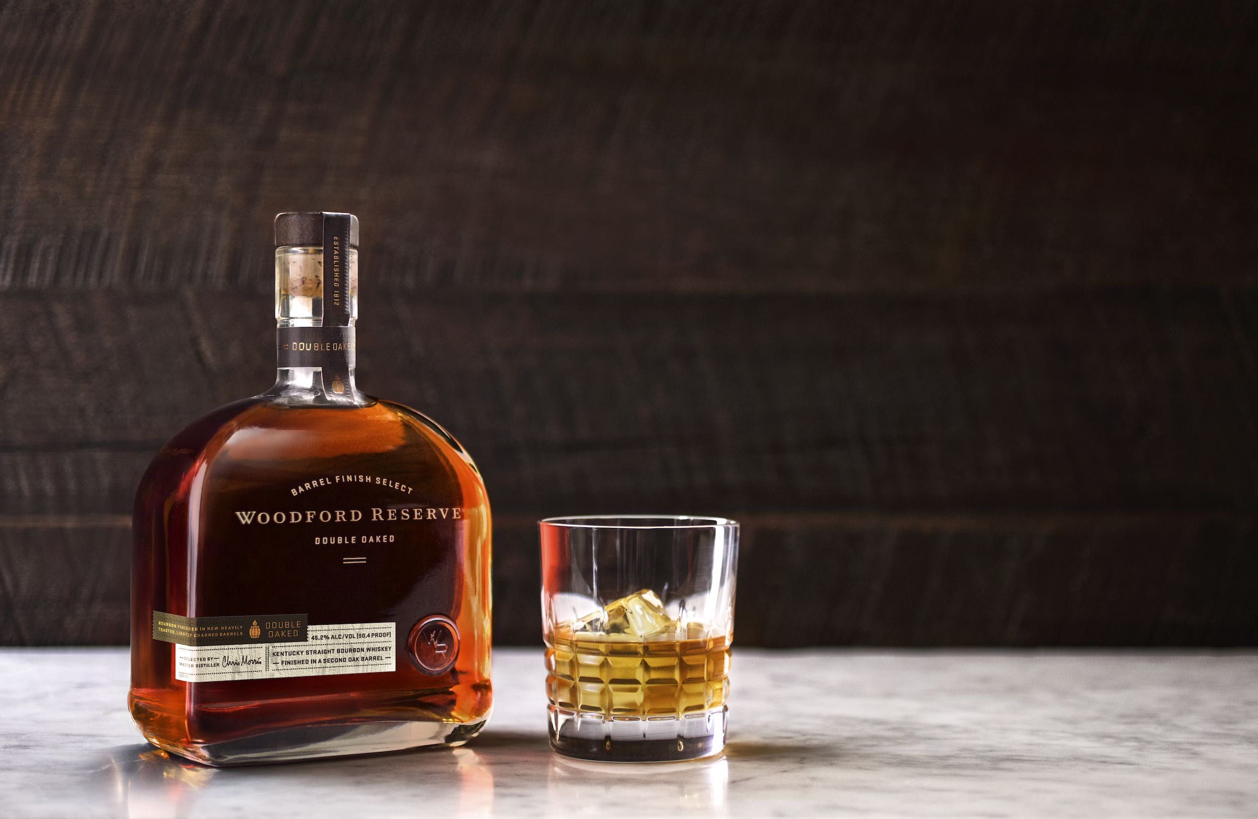 Jody Horton Photography - Woodford Reserve double oaked Bourbon Whiskey Ad with bottle and tumbler on marble surface.