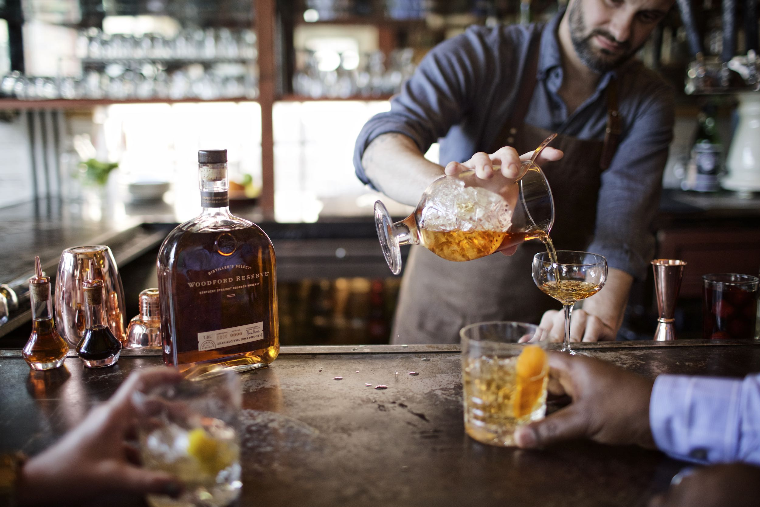 Jody Horton Photography - Woodford Reserve Bourbon Whiskey Ad with bartender pouring into a coupe glass.