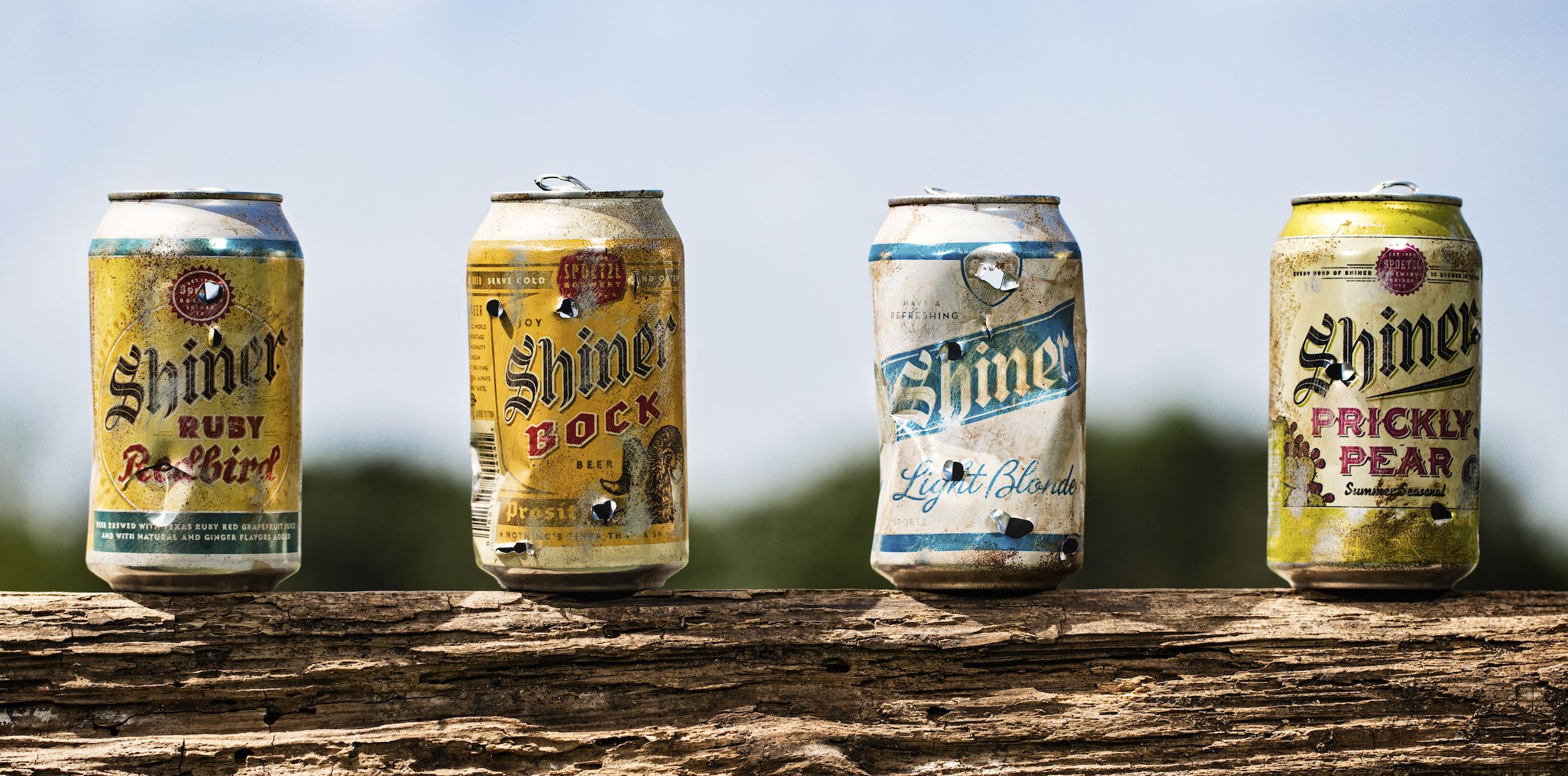 Jody Horton Photography - Shiner Beer Can Ad showing four cans on a fence post with holes from being shot by a BB gun.