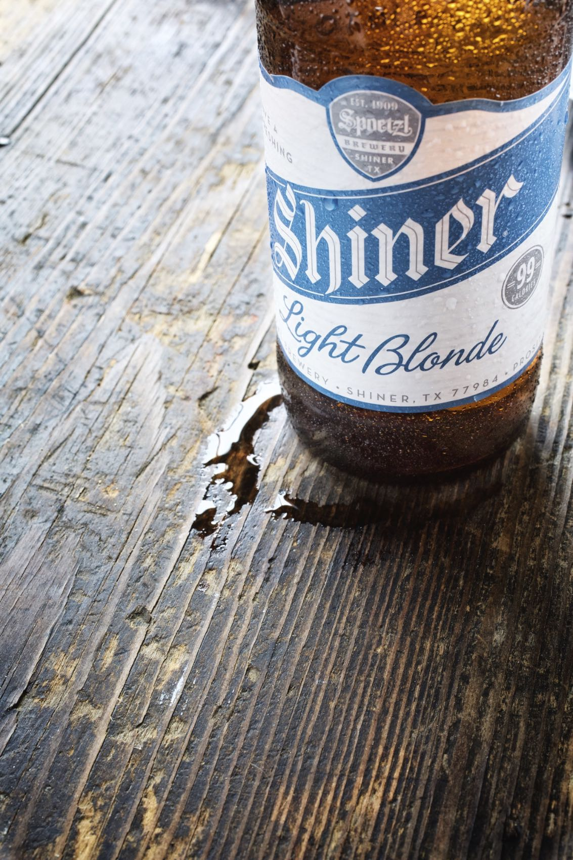 Jody Horton Photography - Shiner Light Blonde ad with cold bottle and condensation on wood table for McGarrah Jessee.