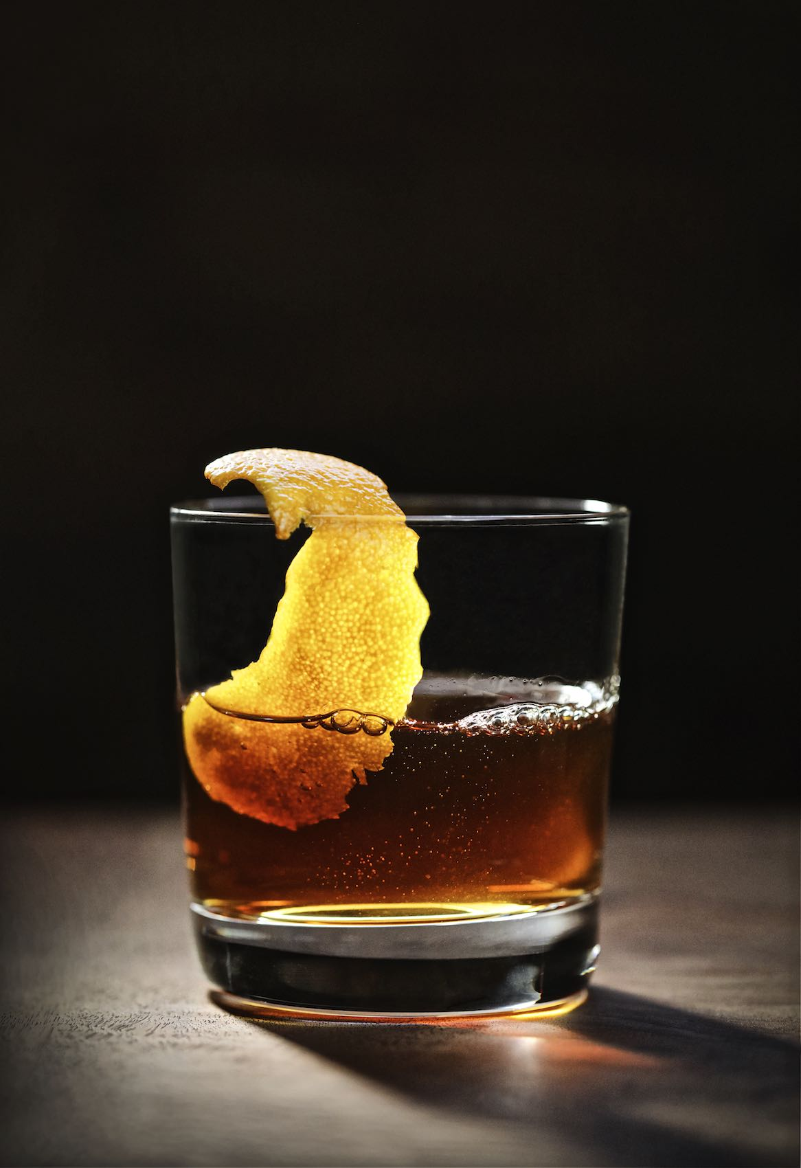 Jody Horton Photography - Whisky with large orange peel on wood table