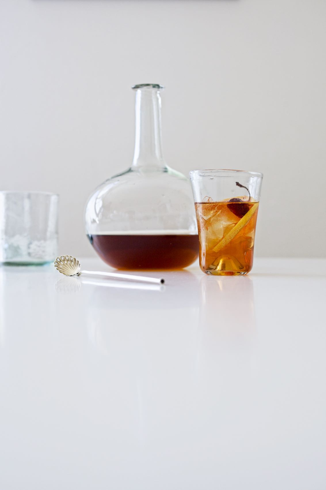 Jody Horton Photography - Bottle and classic bourbon cocktail on white table for Food & Wine.