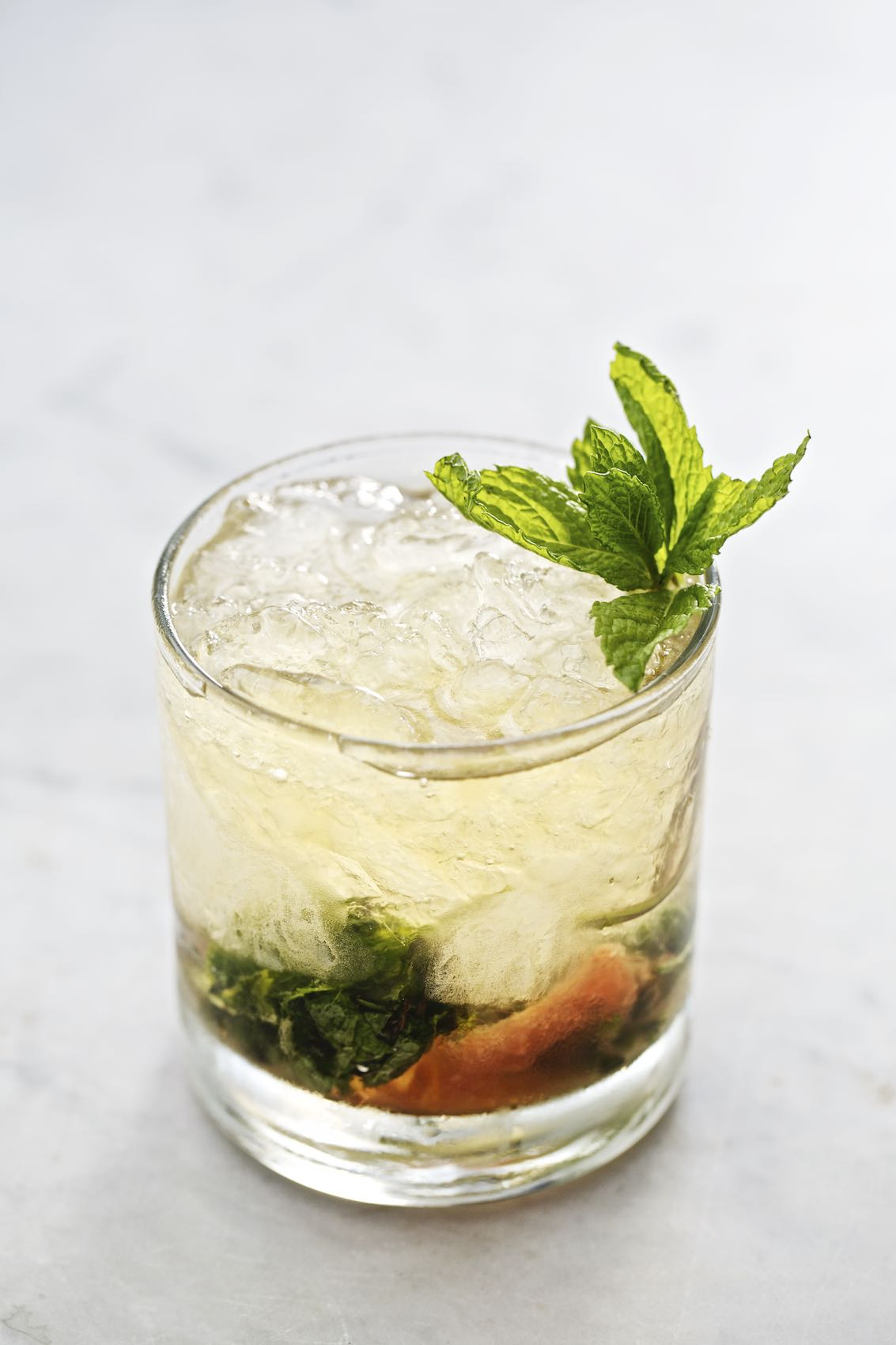 Jody Horton Photography - Iced cocktail with mint garnish on white table.