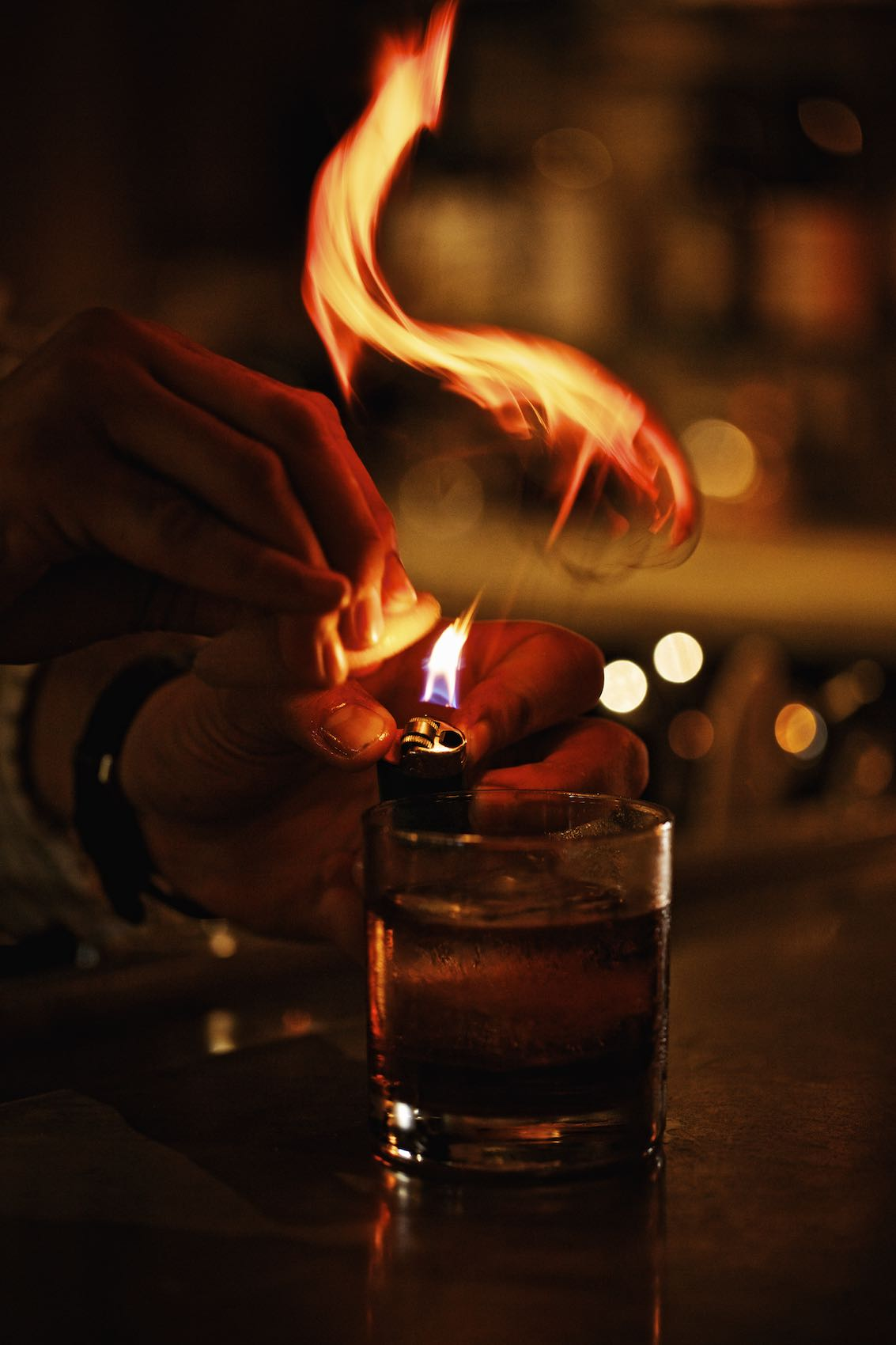 Jody Horton Photography - Bartender hands preparing a flaming cocktail.