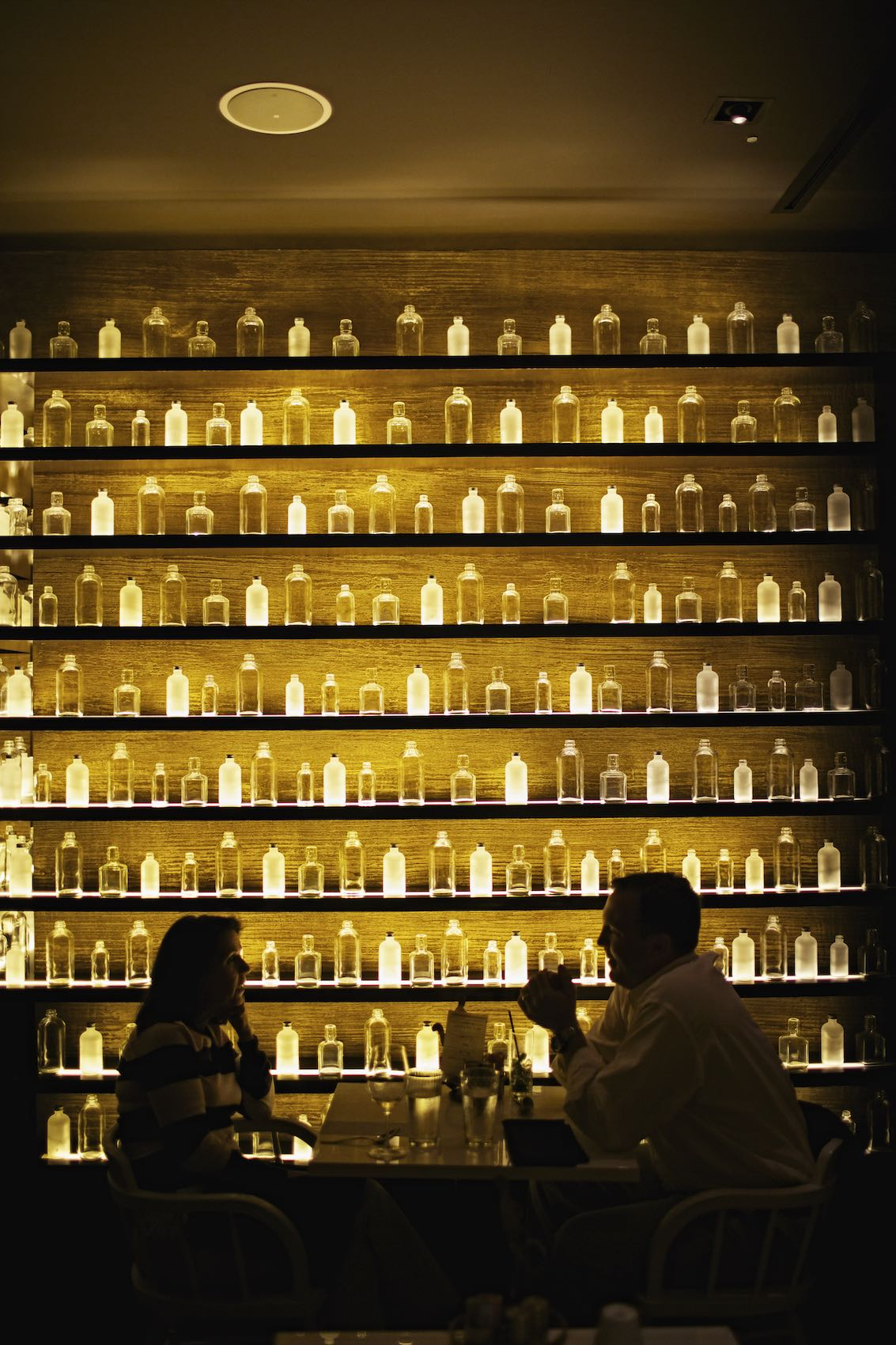 Jody Horton Photography - Profiles of guests against brightly lit New Orleans bottle wall.