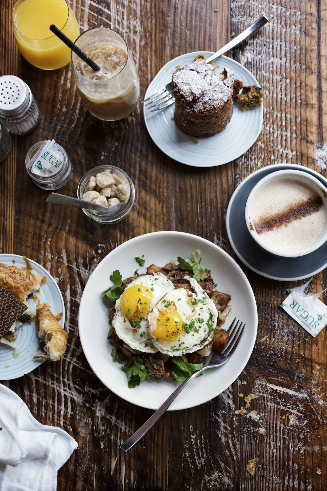 Jody Horton Photography - Breakfast spread and coffees on a wooden table.