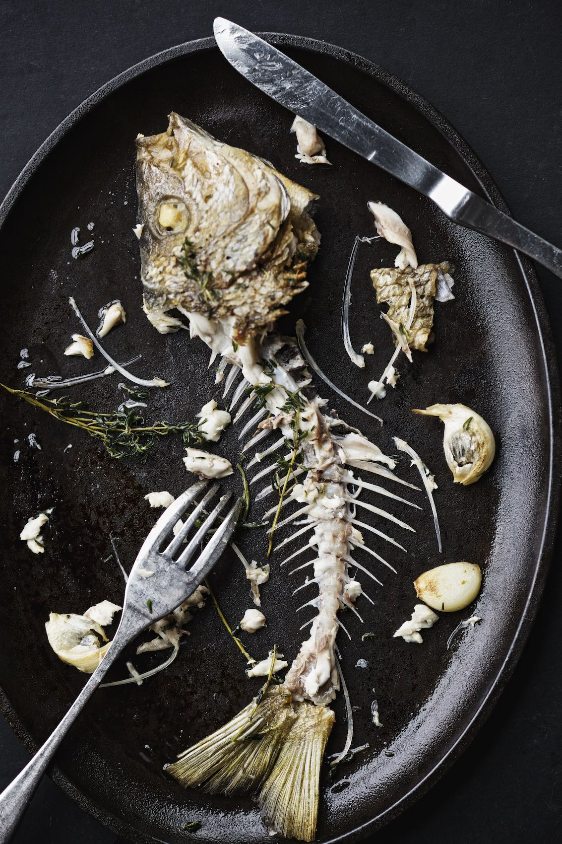 Jody Horton Photography - Remnants of a whole, cooked fish on a black skillet.