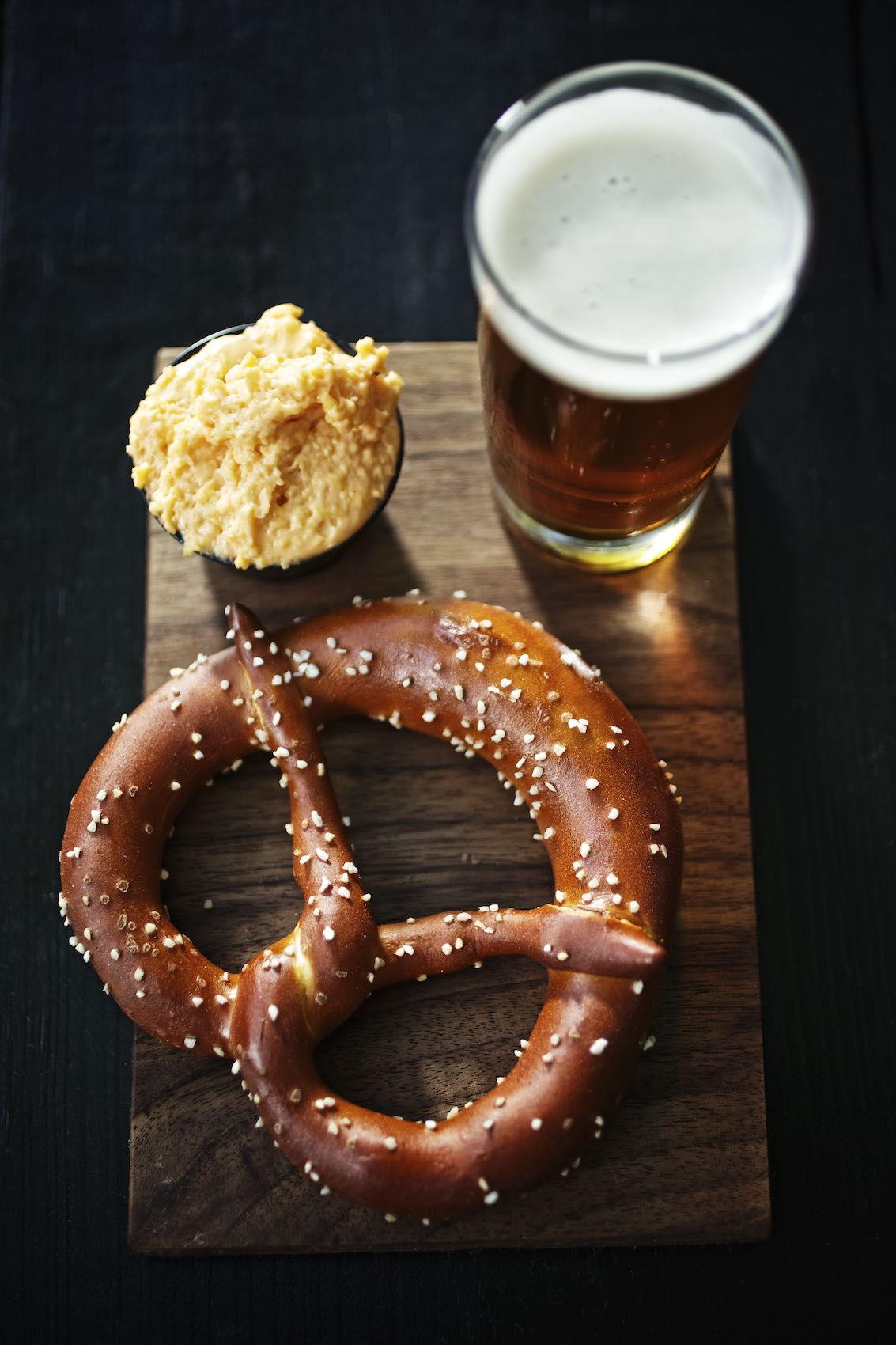 Jody Horton Photography - Baked pretzel, cheese sauce, and draft beer on a wooden board.