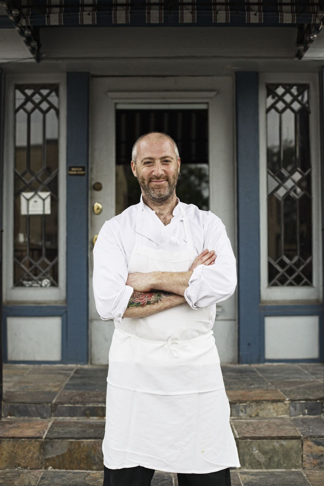 Jody Horton Photography - Chef in uniform proudly standing outside storefront.