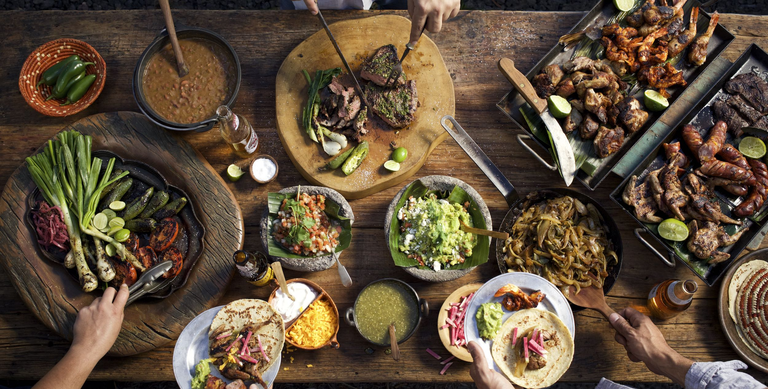 Jody Horton Photography - Taco spread on a wooden table with hands reaching and plating food.