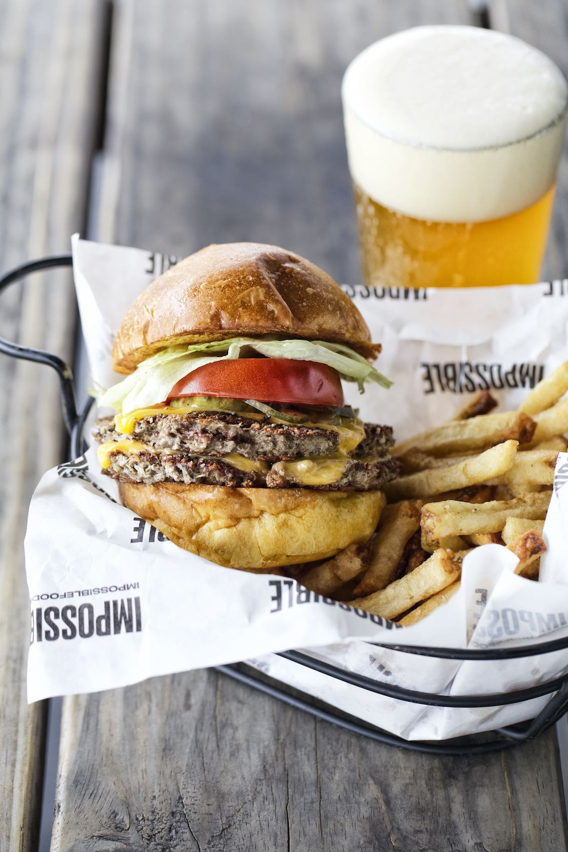 Jody Horton Photography - Basket with a double burger and fries on a wooden picnic table.
