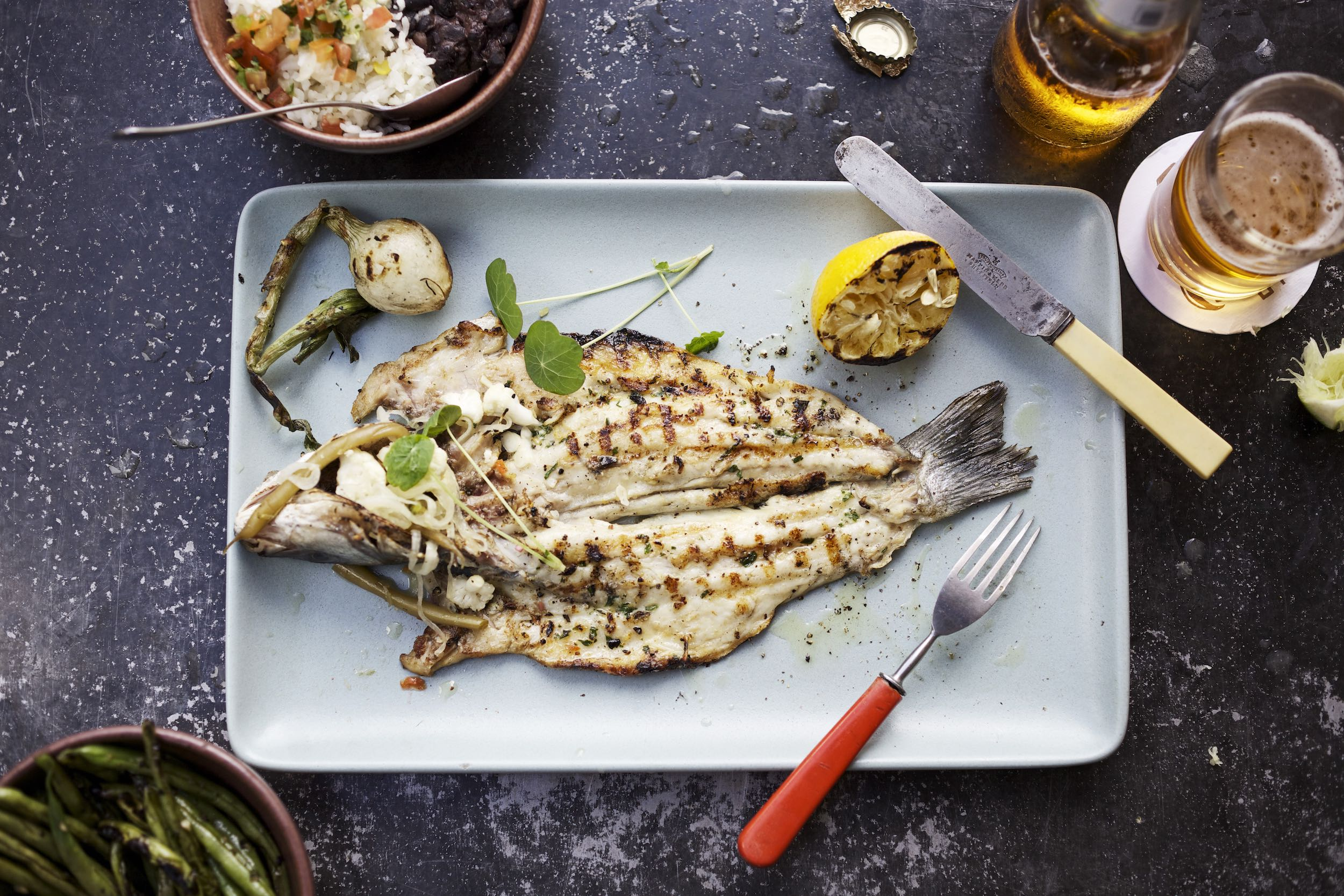 Jody Horton Photography - Whole, grilled fish on a light blue plate with grilled accompaniments.
