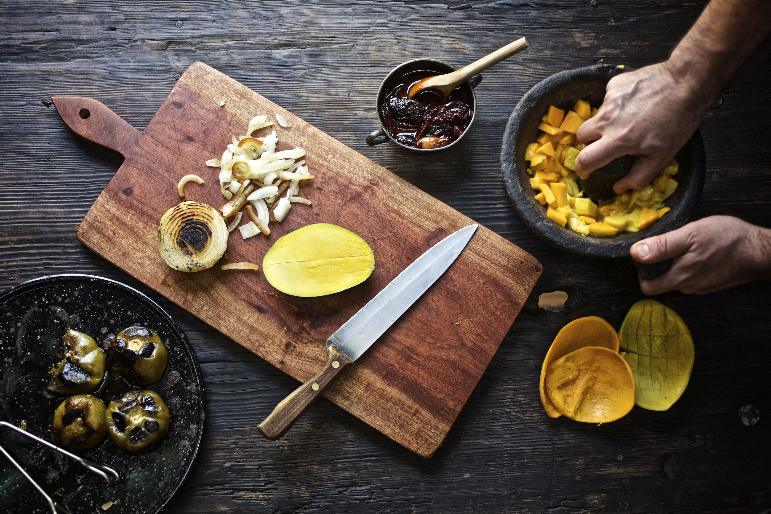 Jody Horton Photography - Chef hands preparing ingredients on a wood cutting board.