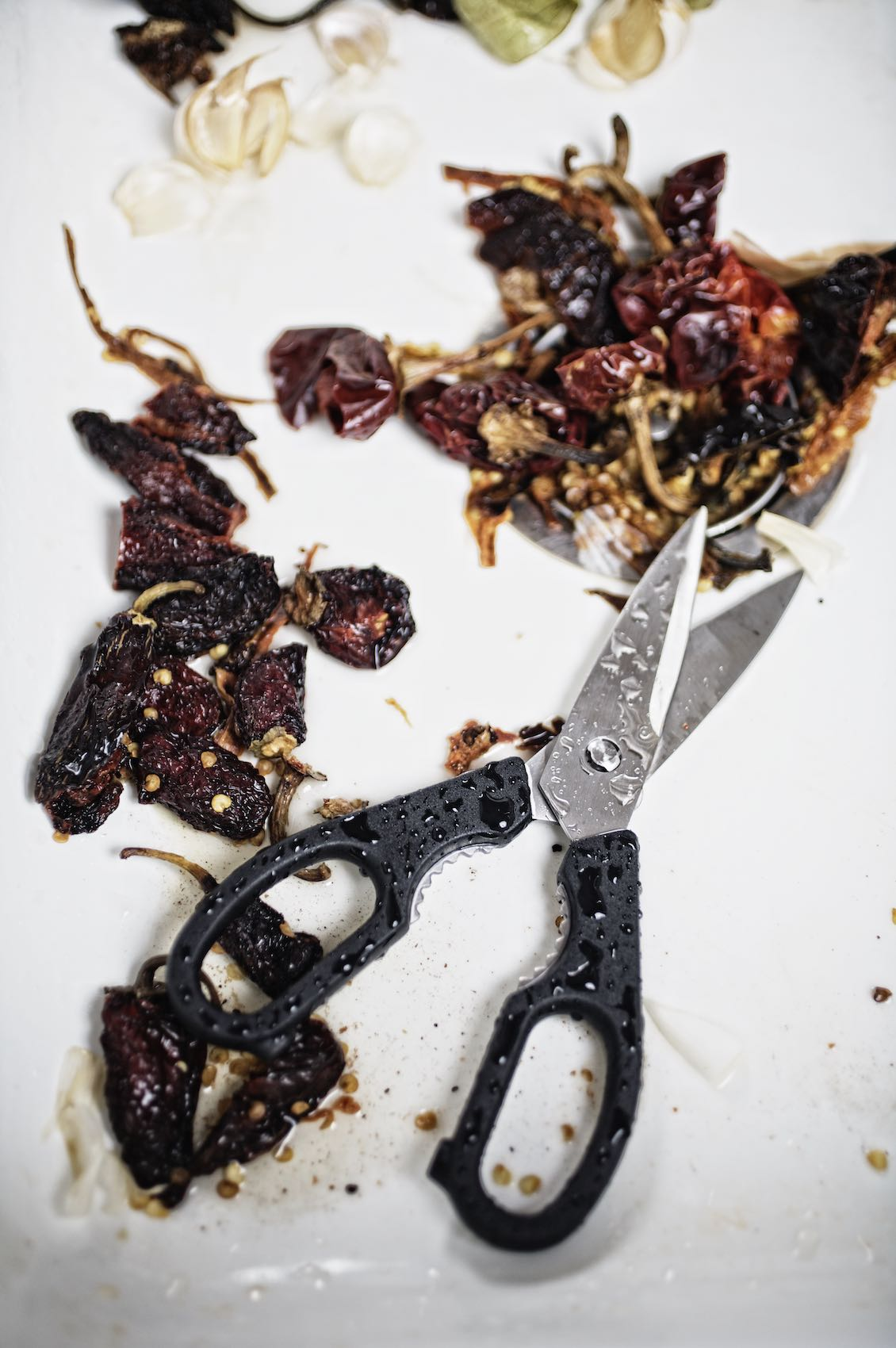 Jody Horton Photography - Scissors cutting dried chilis on a white surface.