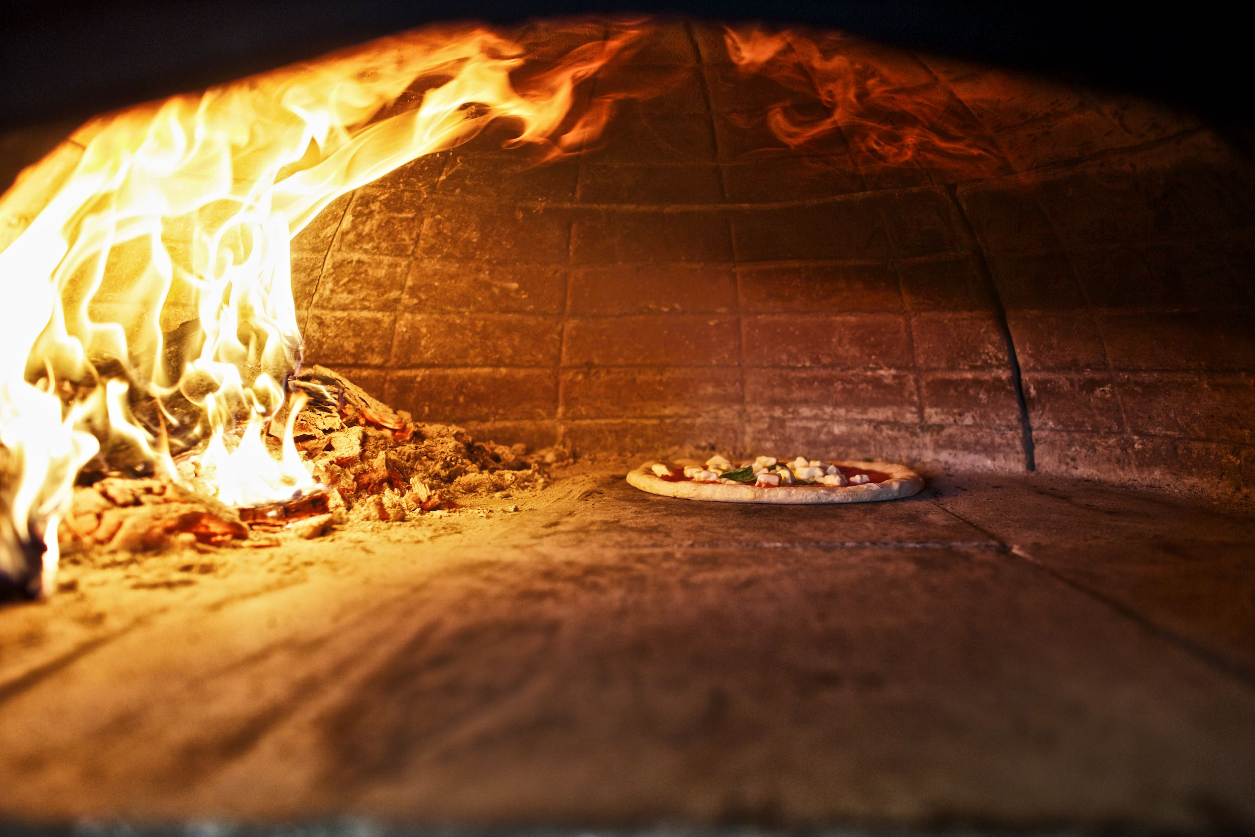 Jody Horton Photography - Pizza cooking in domed oven next to large flames.