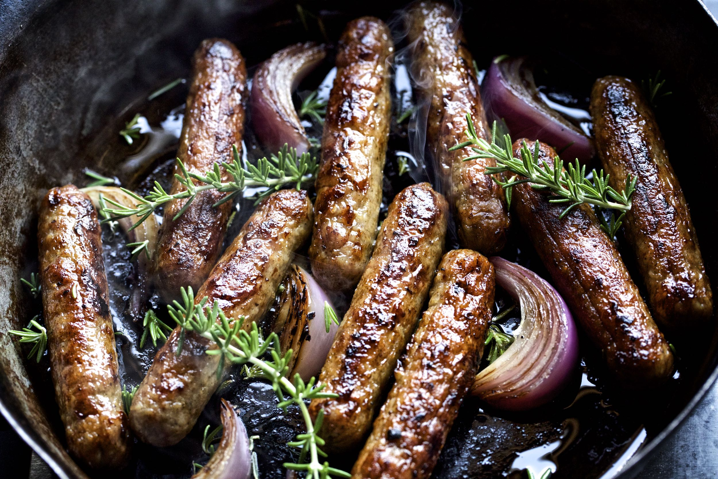 Jody Horton Photography - Sausage links cooking with onions and rosemary in rustic skillet.