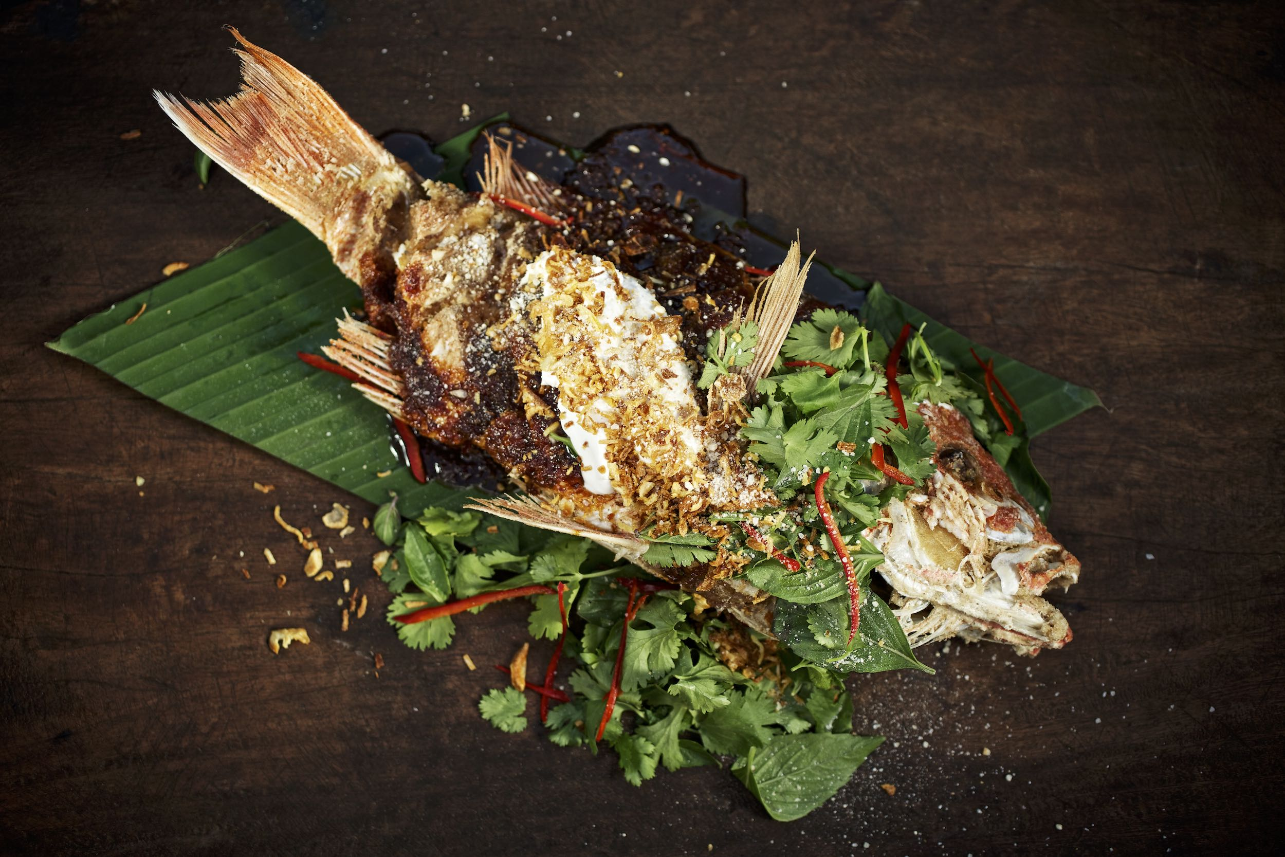 Jody Horton Photography - Whole cooked redfish on banana leaf with herbs and sauces.