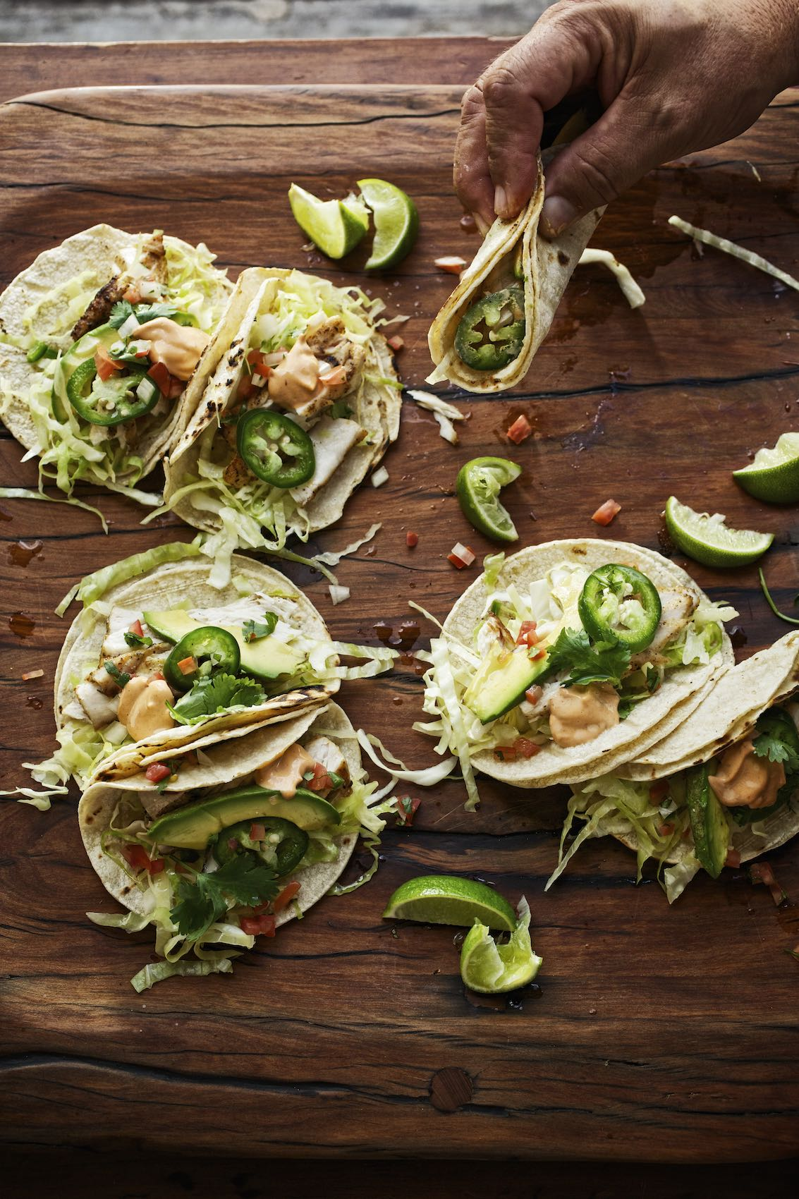 Jody Horton Photography - Assorted tacos with lime on wood surface.