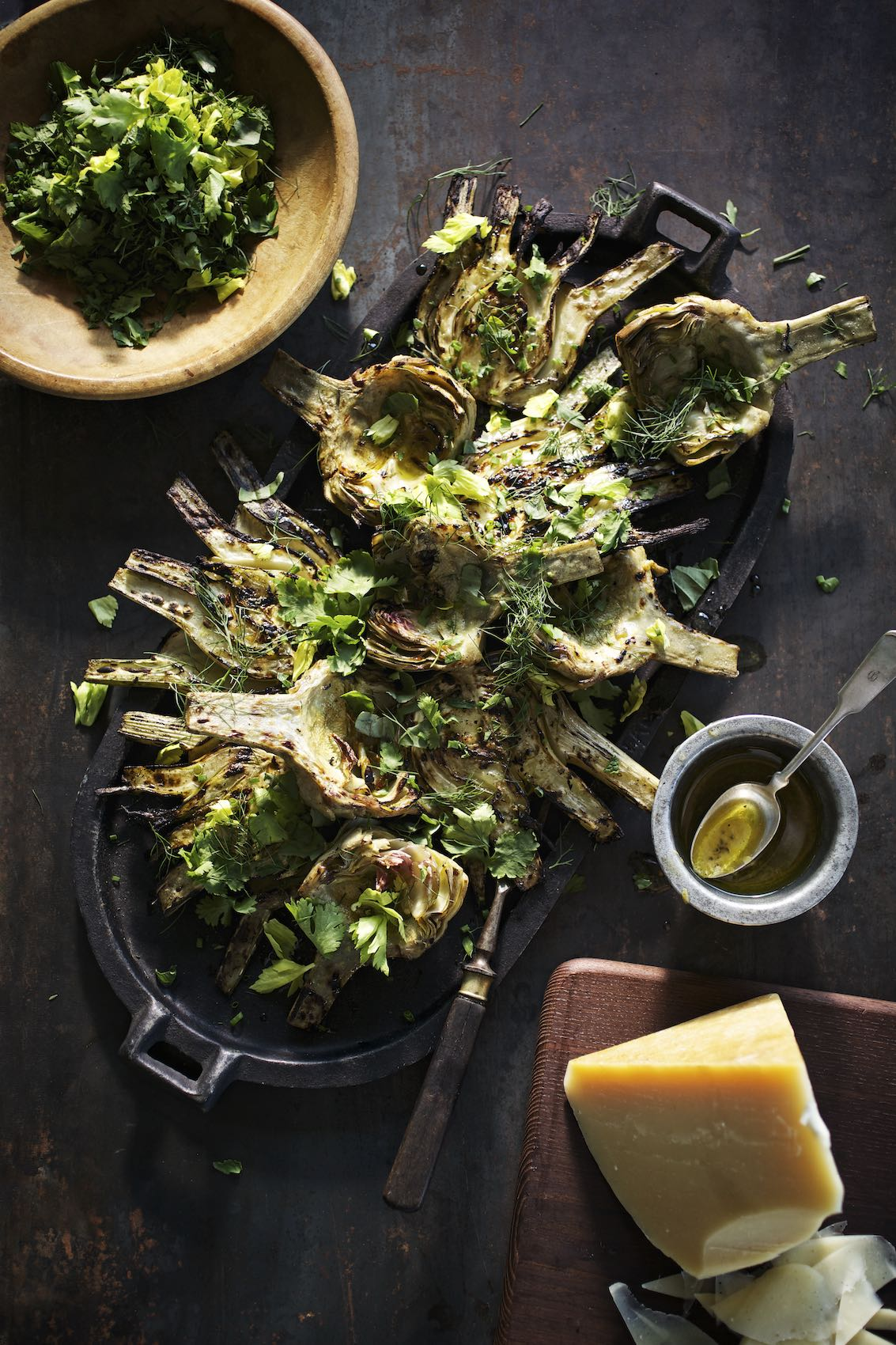 Jody Horton Photography - Grilled fennel and artichoke in cast iron pan on wood table.
