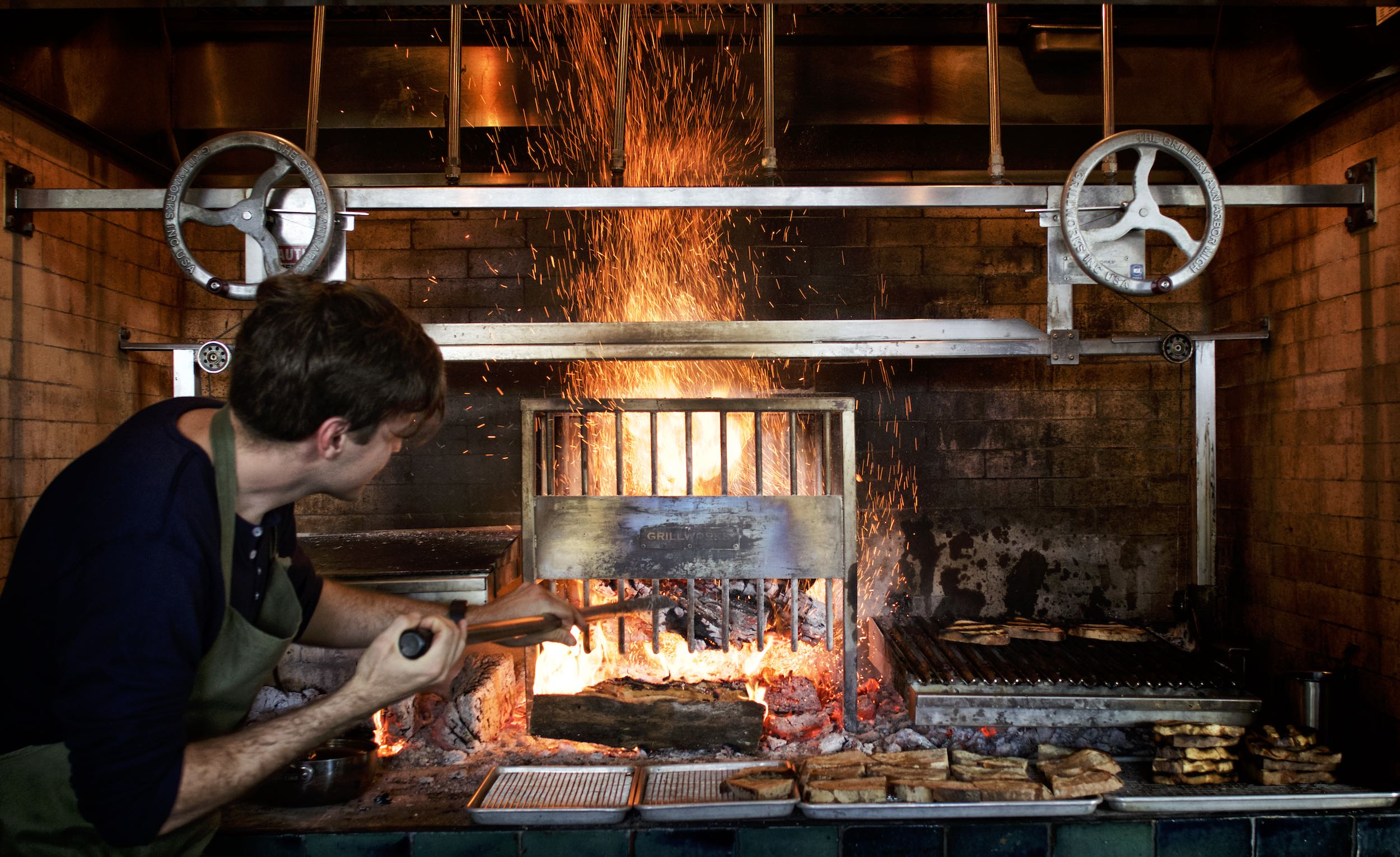 Jody Horton Photography - Chef stoking fire in brick oven.