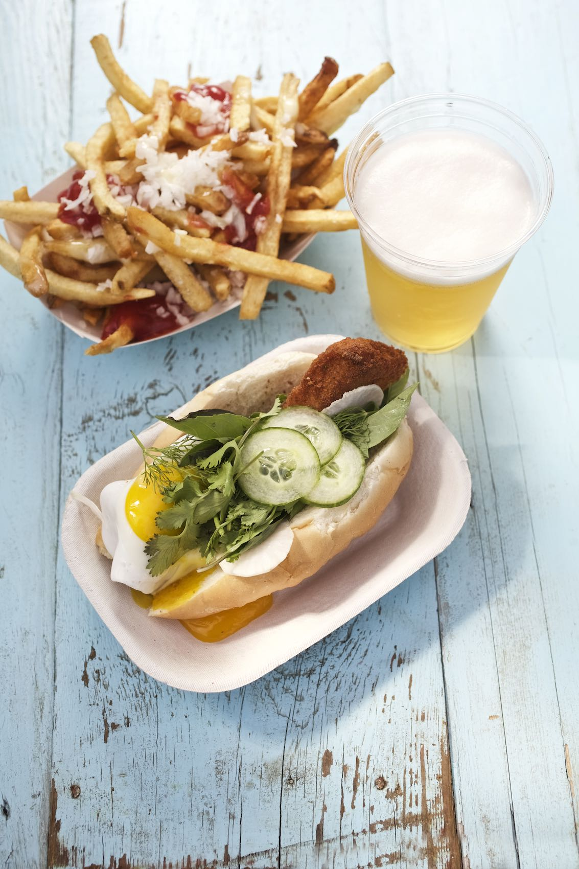 Jody Horton Photography - Bahn Mi sandwich with draft beer and loaded fries on blue picnic table.