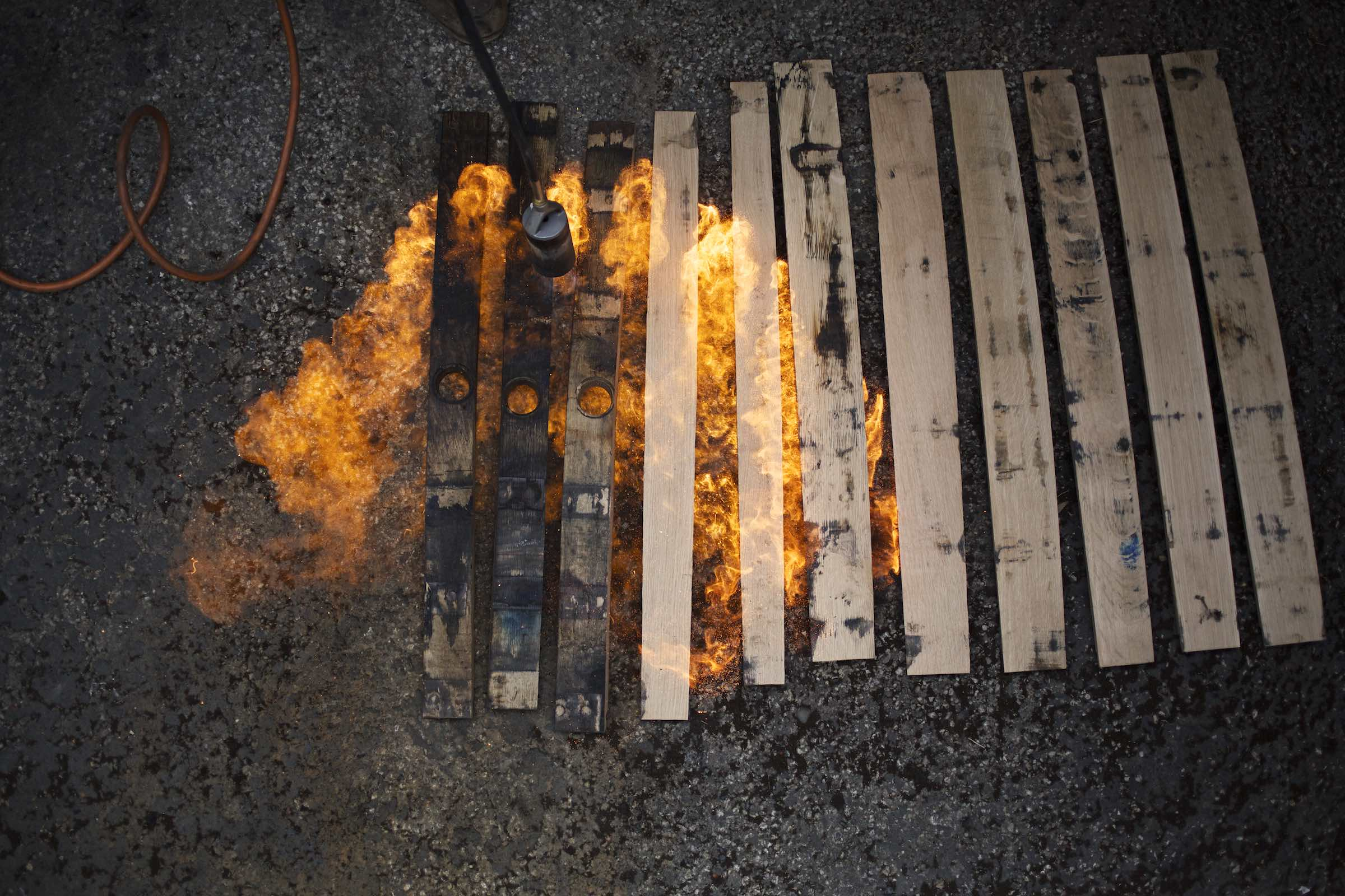 Jody Horton Photography - Flames burning wood planks placed on asphalt.