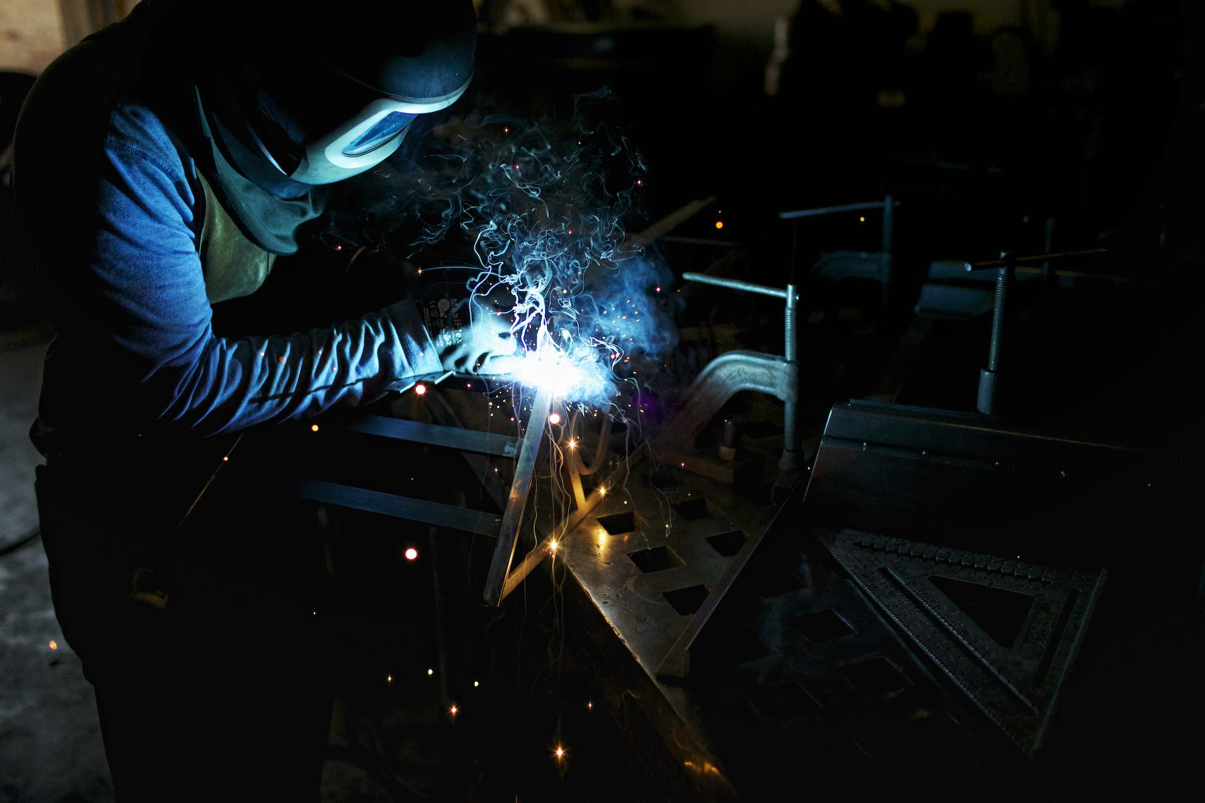 Jody Horton Photography - Welder working on a piece of metal creating blue flames and sparks,