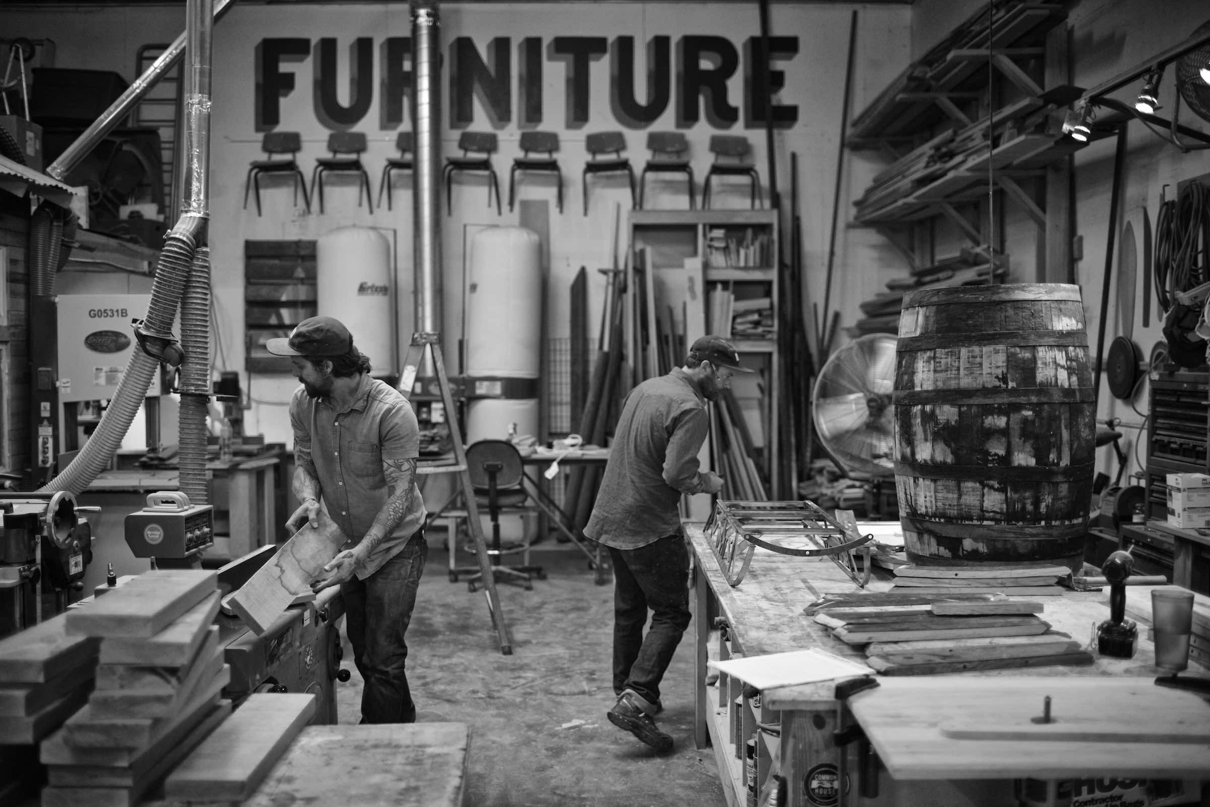 Jody Horton Photography - Woodworker sanding down a sled in his workshop, shot in B&W.