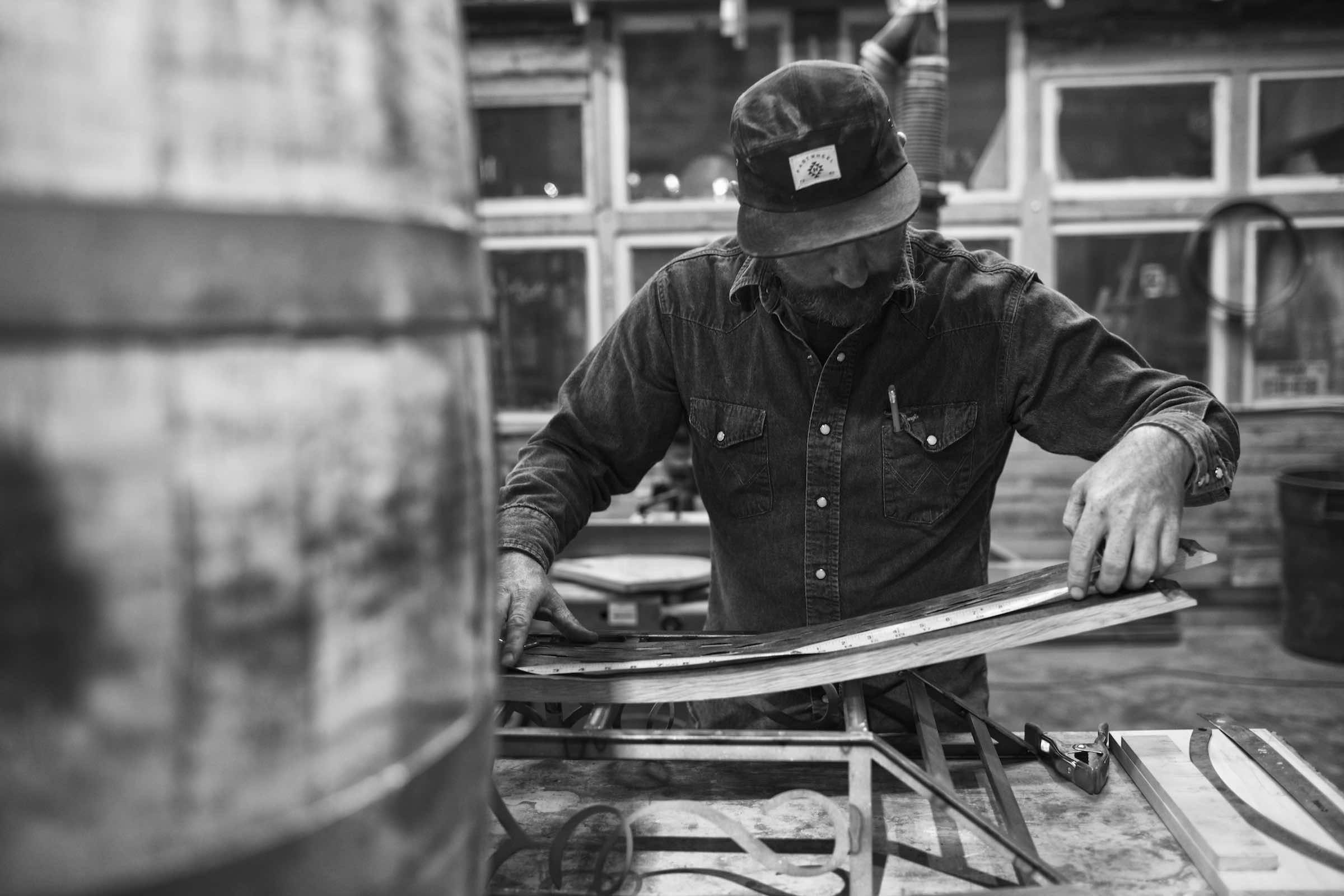 Jody Horton Photography - Builder using a measuring tape in the workshop, shot in B&W.