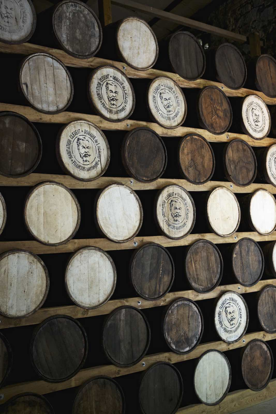 Wooden rum barrels stacked high on wood planks.
