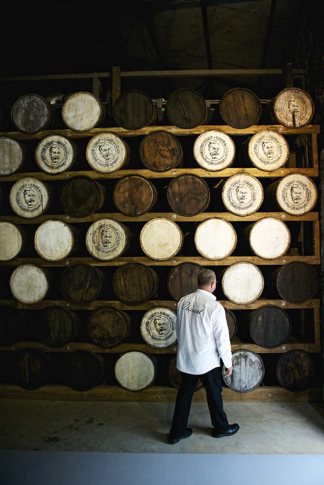 Jody Horton Photography - Jody Horton Photography - Formally dressed man observing stacks of wood barrels in the distillery.