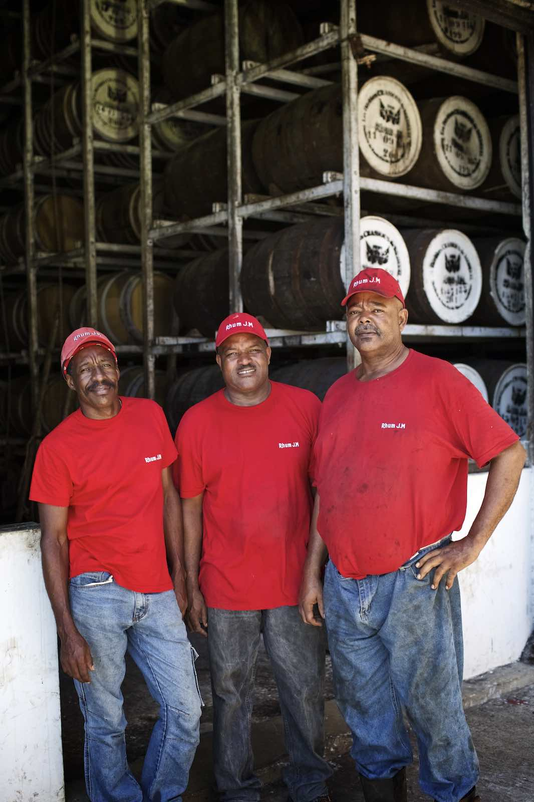 Jody Horton Photography - Workers red labeled caps and shirts standing against stacked wood barrels.