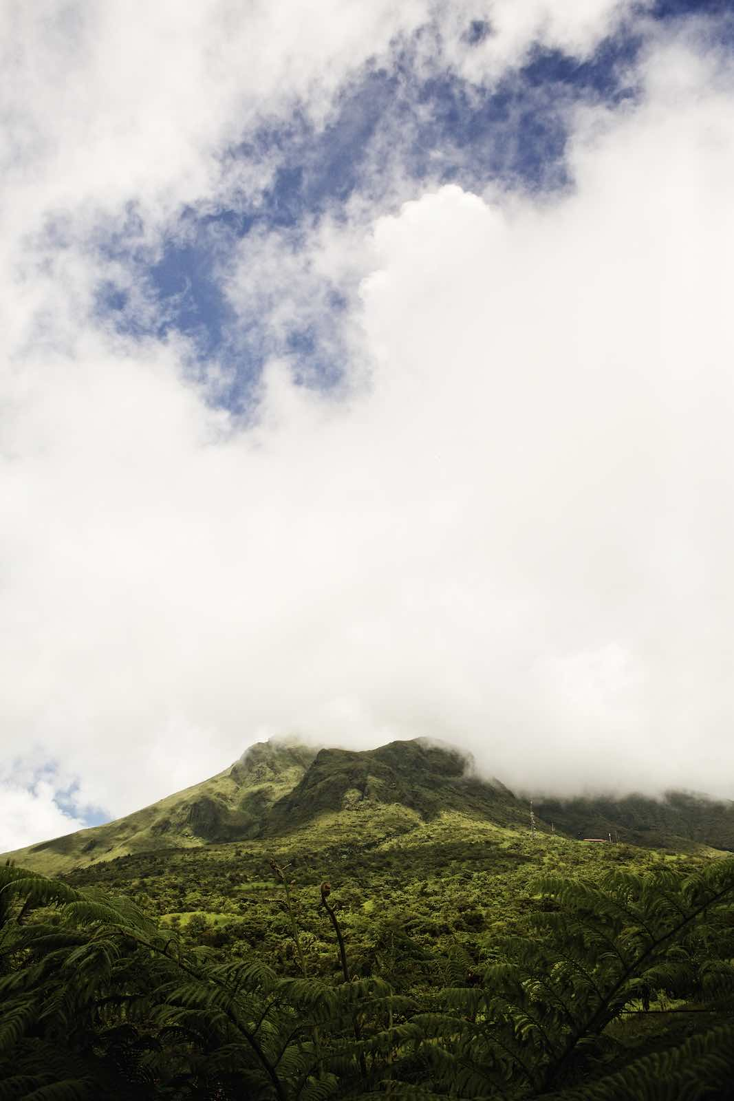 Jody Horton Photography - A lush and tropical mountain with low clouds covering the top.