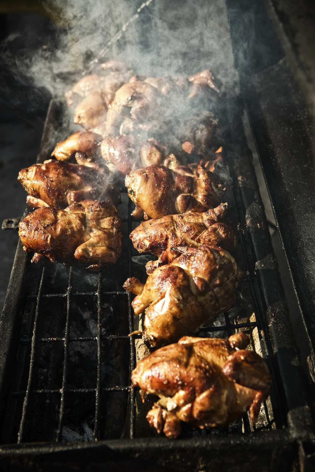 Jody Horton Photography - Chickens cooking on a smokey grill.