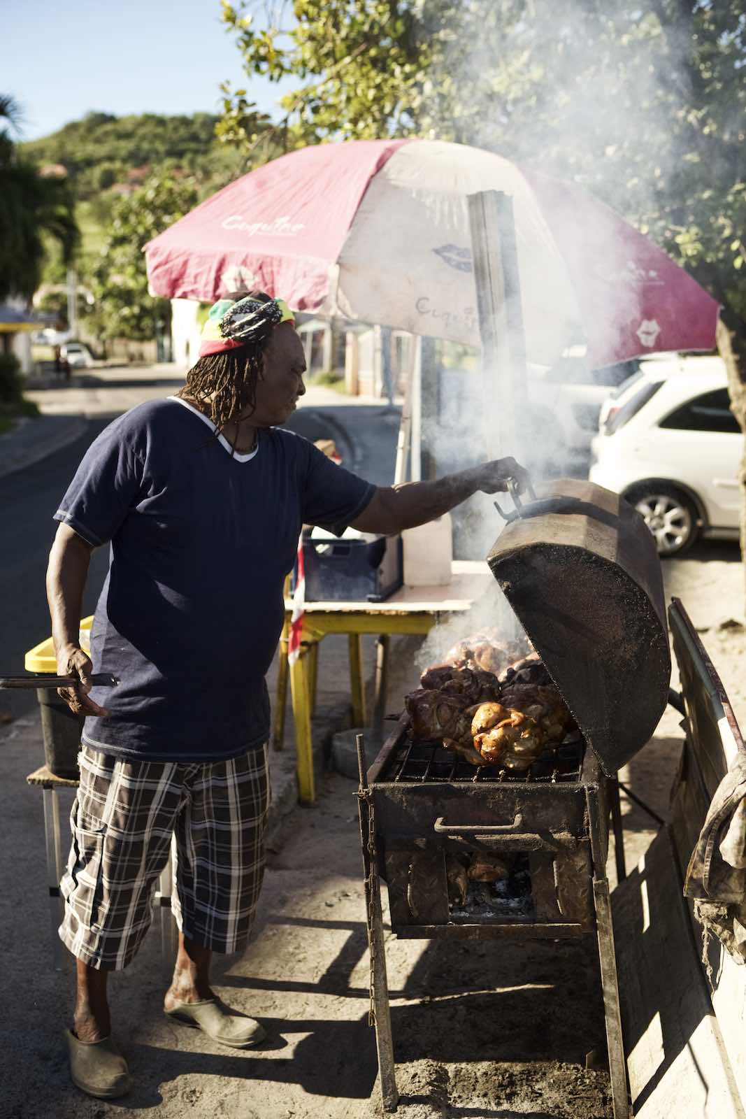 Jody Horton Photography - Man grilling chickens on the street in the bright sunlight.