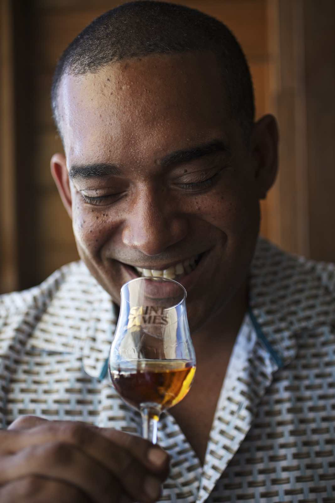 Jody Horton Photography - Man in a patterned shirt smiling while holding a glass of rum.