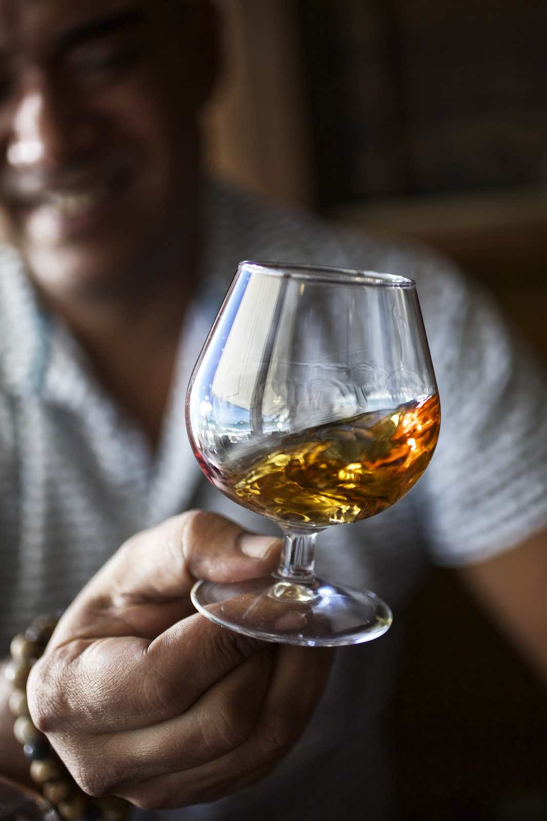Man swirling rum in a short stemware glass.