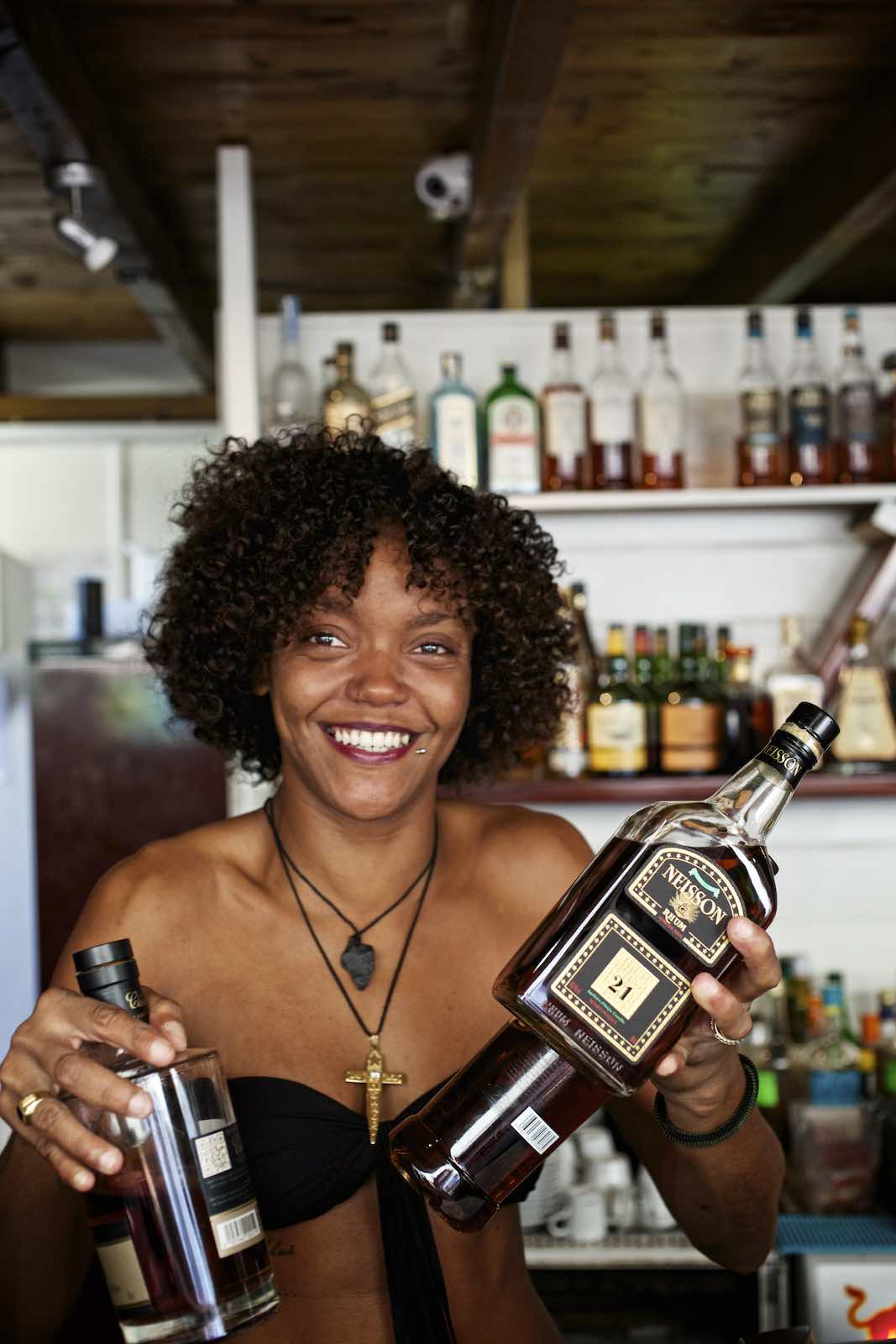 Jody Horton Photography - Bar tender smiling while holding three bottles of rum behind the bar.