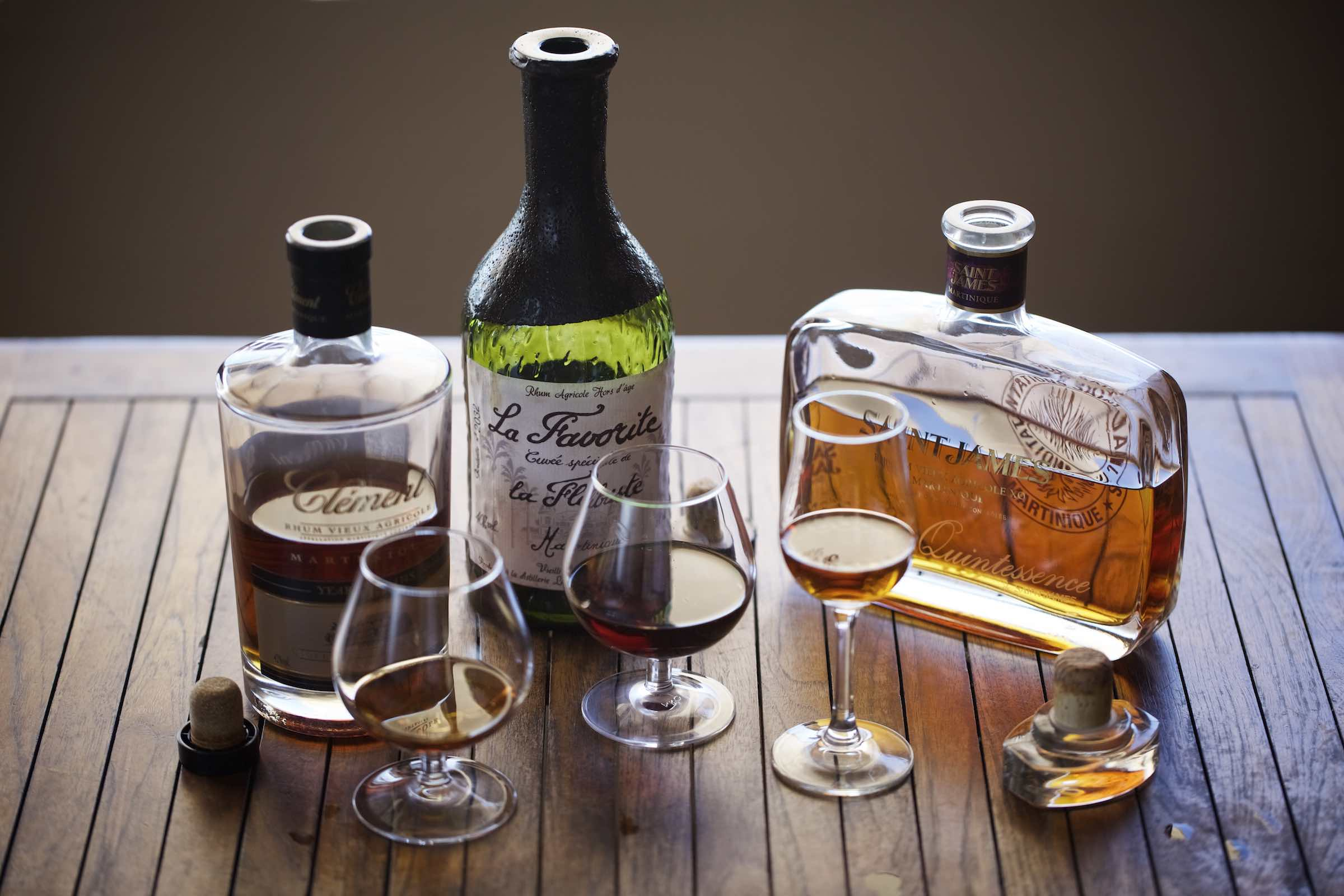 Assorted rum bottles with each rum poured in a stemware glass.