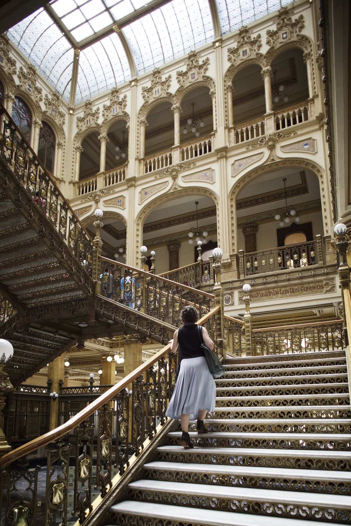 Jody Horton Photography - Woman climbing a golden staircase in Mexico City.