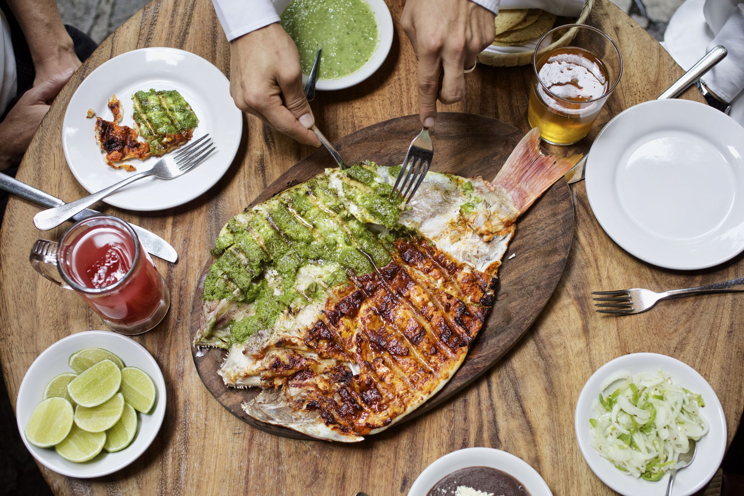 Jody Horton Photography - Mexico City dinner spread with cooked fish and beverages on a wood table.