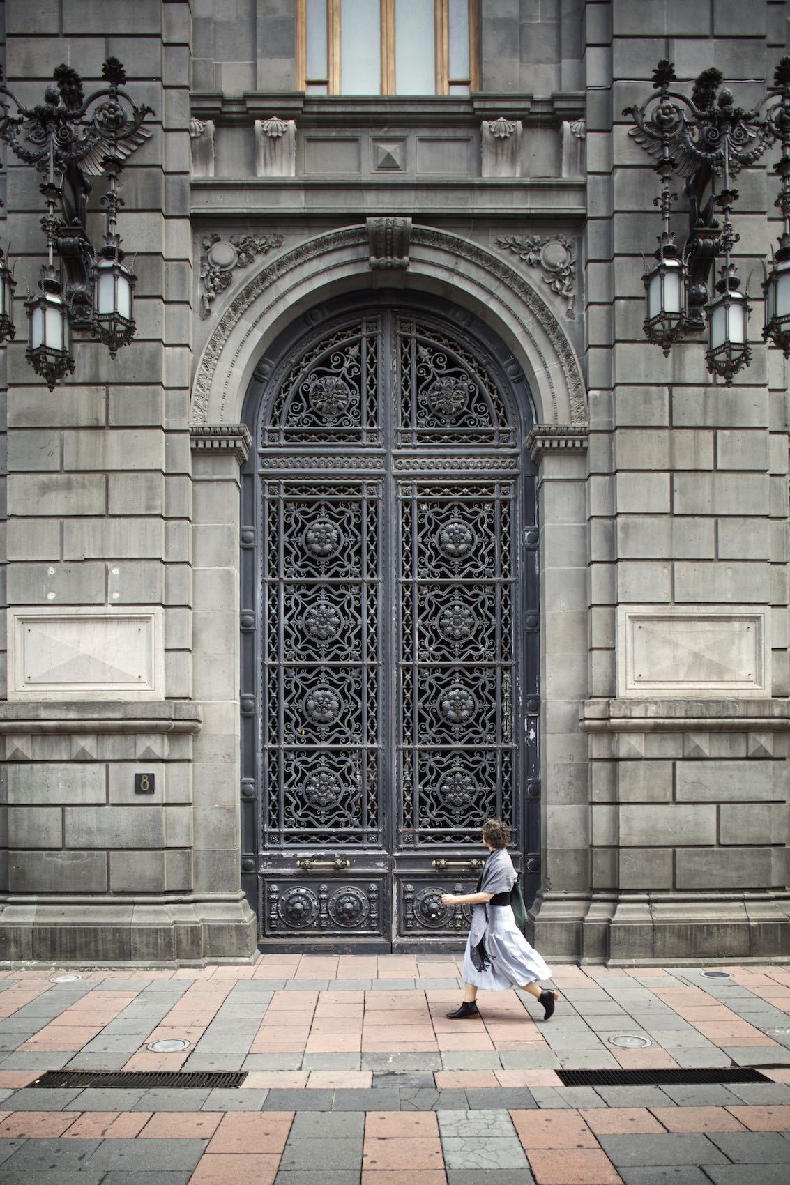 Woman walking in front of a large building in Mexico City.