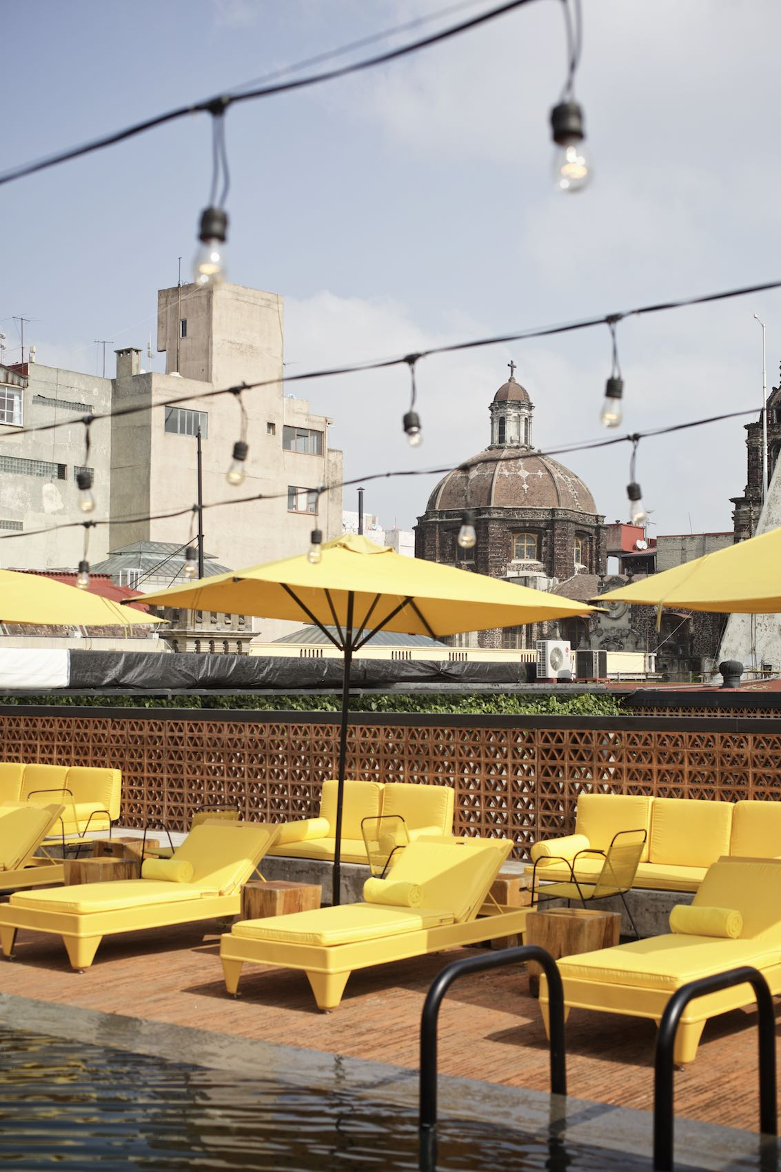 Hotel pool with vibrant yellow furniture in Mexico City.