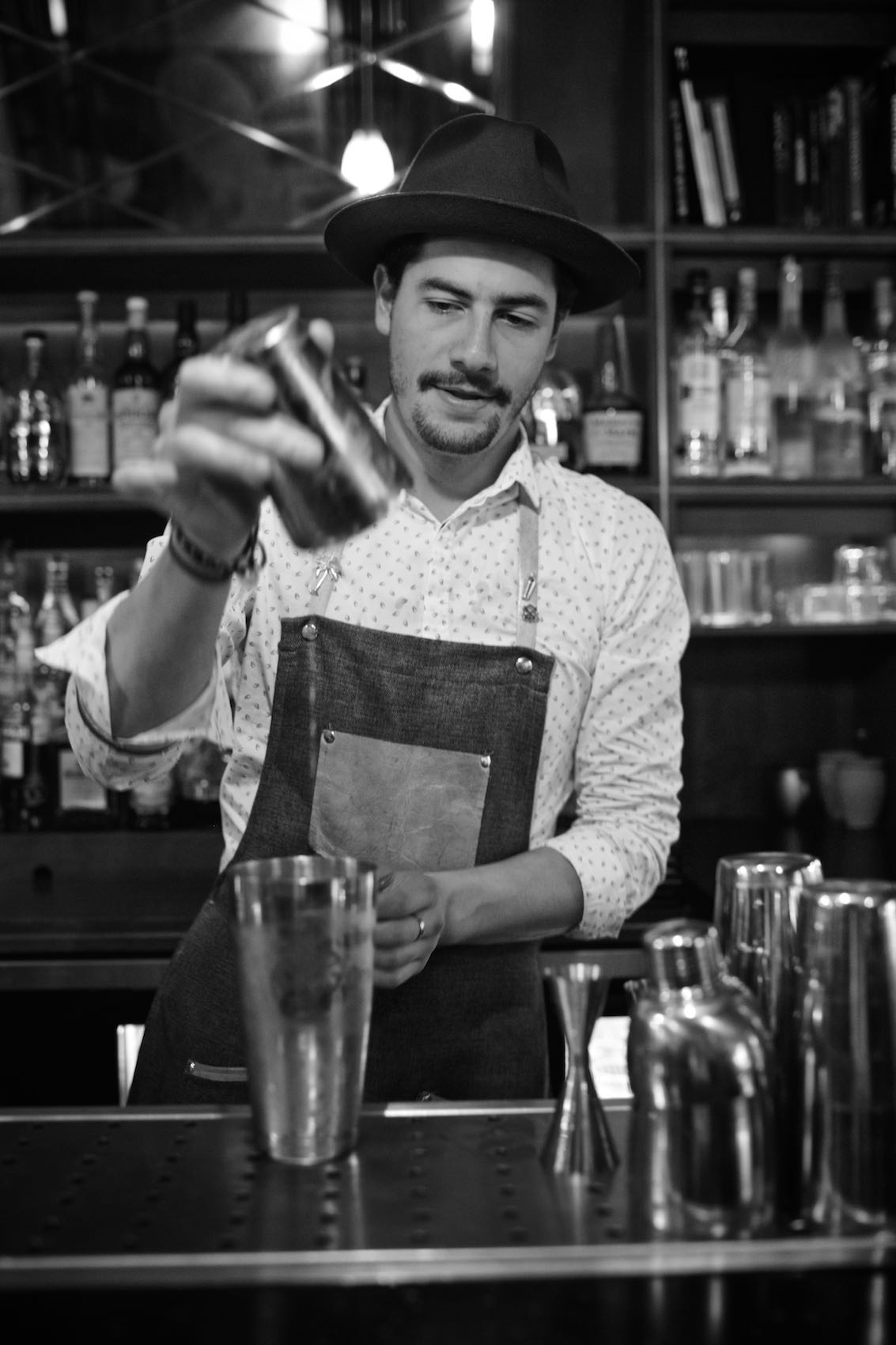 Jody Horton Photography - Bartender preparing cocktails behind a bar, shot in B&W.
