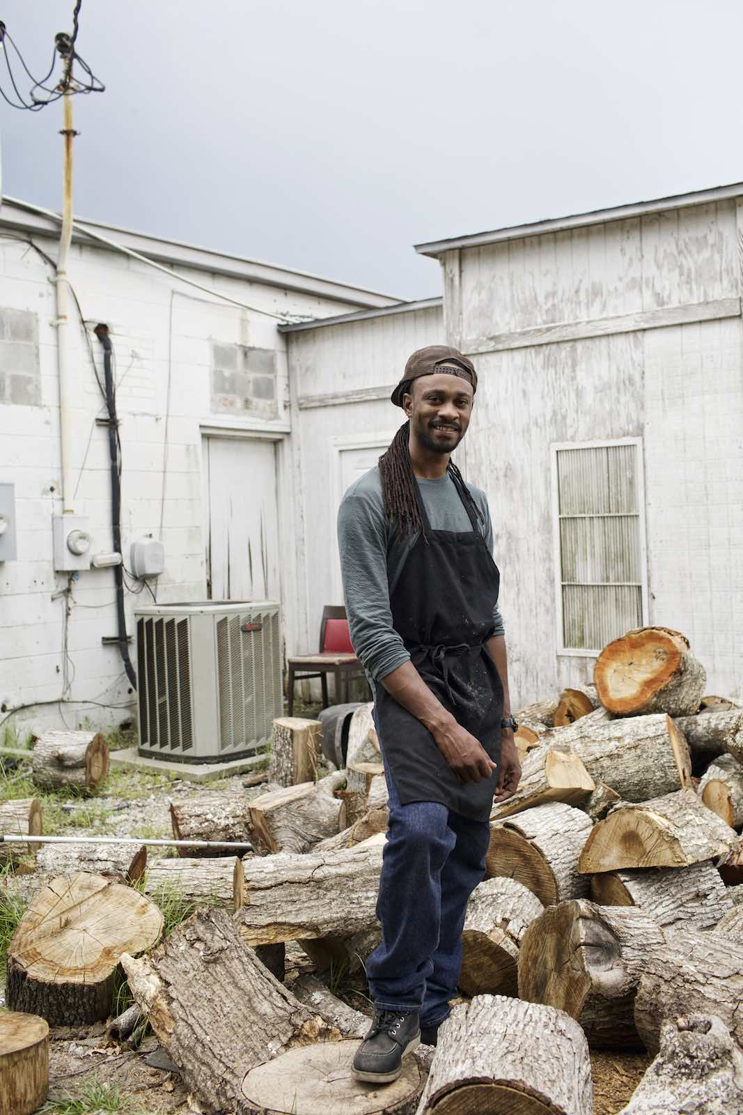 Jody Horton Photography - Cook standing among piles of chopped wood.