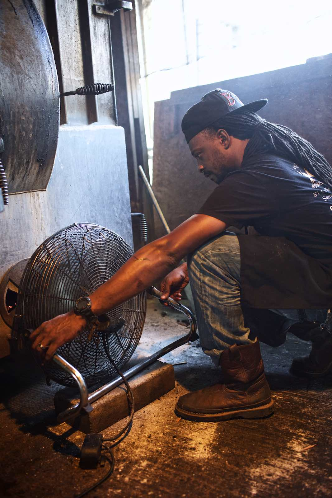 Chef adjusting fan in an open kitchen.