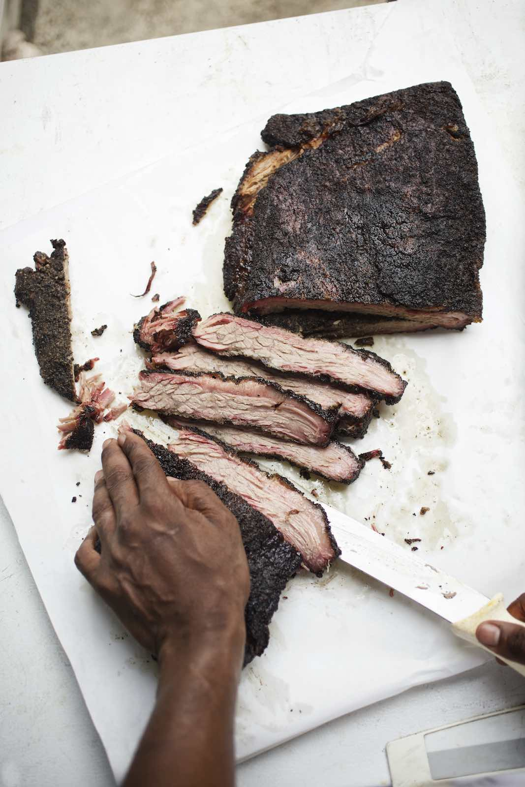 Jody Horton Photography - Smoked brisket being sliced on white parchment.