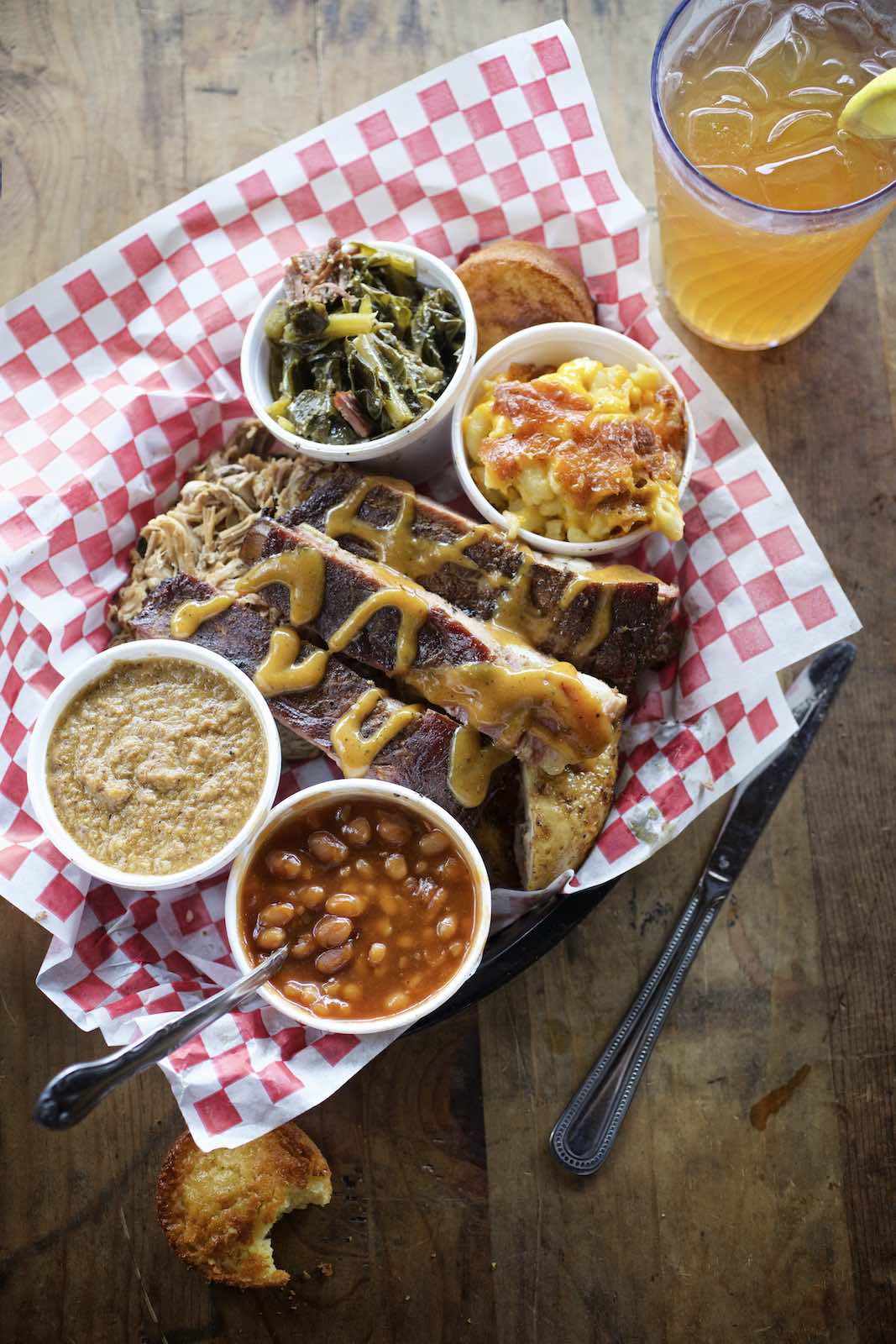Barbecue plate with beans and collards on checkered parchment.